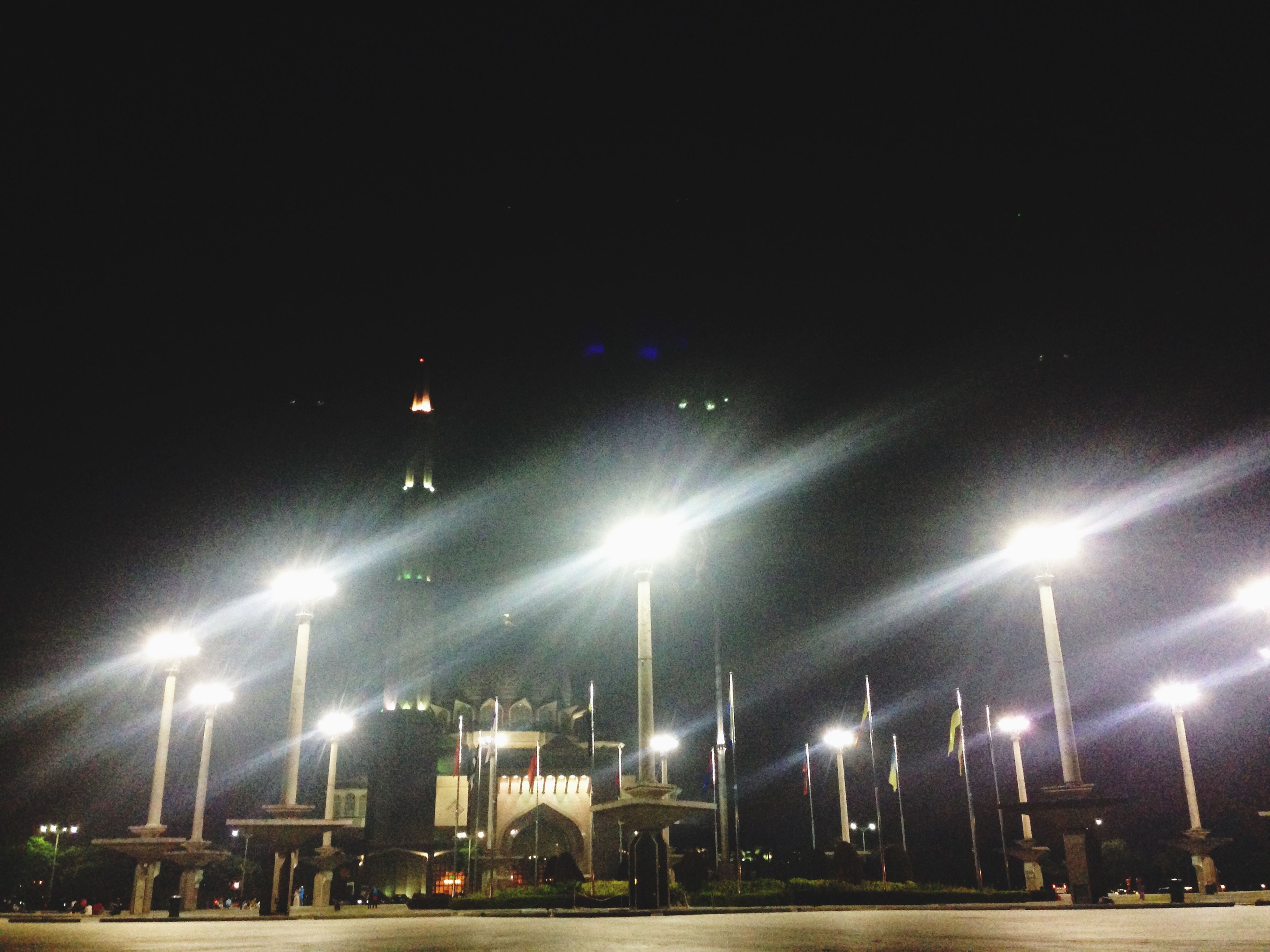 illuminated, night, street light, lighting equipment, built structure, building exterior, architecture, city, transportation, sky, light - natural phenomenon, clear sky, mode of transport, outdoors, street, low angle view, electric light, no people, in a row, copy space