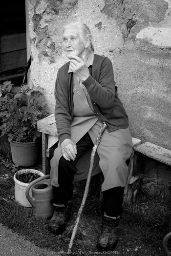 old woman BW 5 Alpine Black & White Black&white Blackandwhite Casual Clothing Country Life Day Expression Face Grey Hair Life Experience Mature Adult Monochrome Narrative Old Woman Portrait Outdoors Outside Person Sitting Sitting On A Bench Talking Talking With Hand Telling Stories
