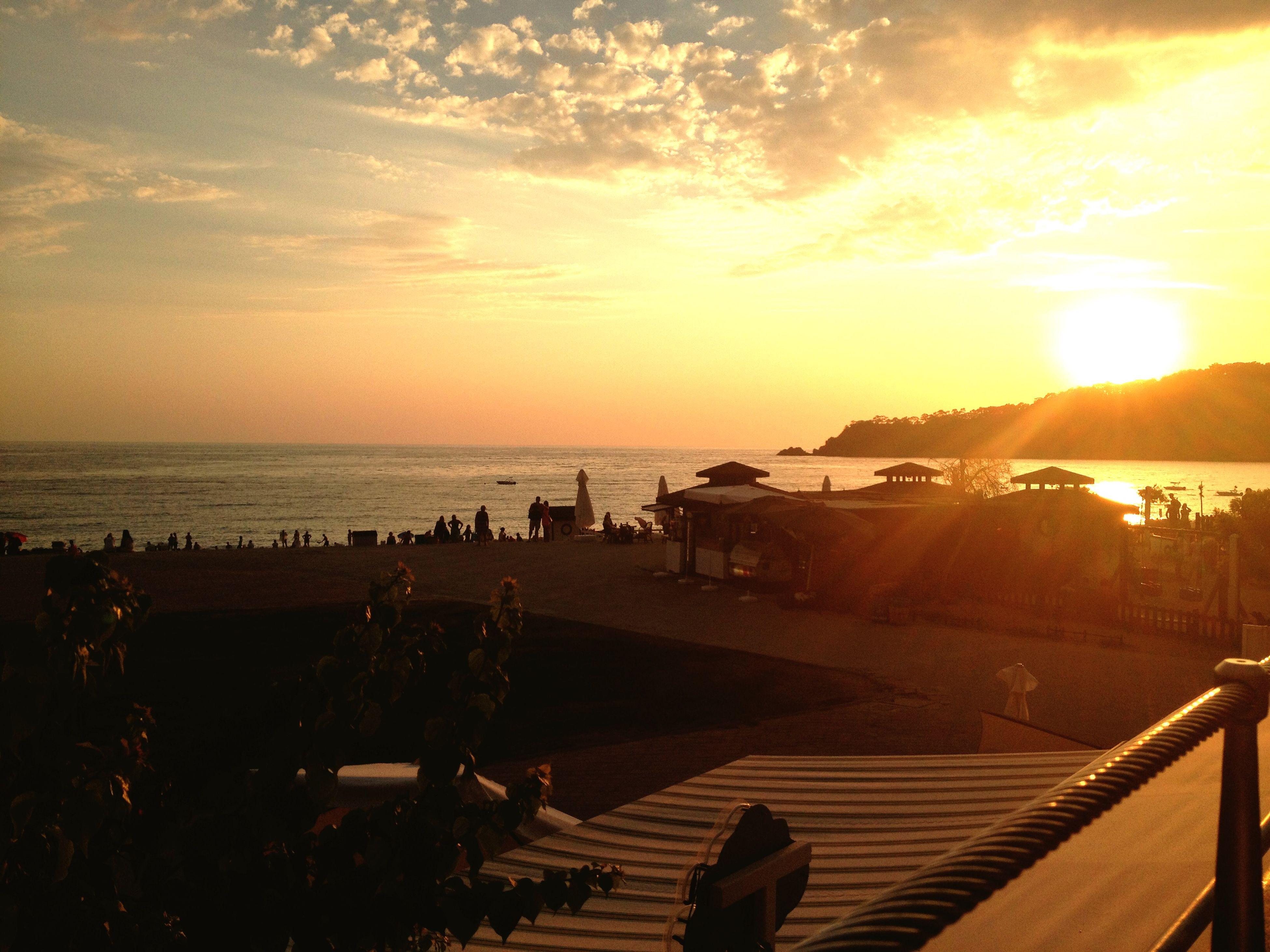 sea, water, sunset, horizon over water, beach, sun, sky, scenics, sunlight, beauty in nature, tranquil scene, shore, tranquility, nature, the way forward, incidental people, sand, idyllic, railing, pier