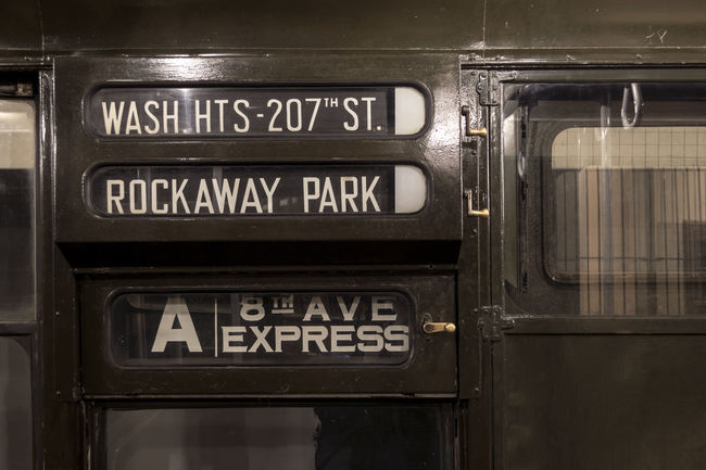 The interior of a restored World War 2 era subway from New York City. The sign is the stops the train will make. 1940's 8th Avenue  Communication Information Sign New York City Public Transport Railroad Station Retro Rockaway Sign Board Subway Subway Station Text Vintage Washington Heights Western Script