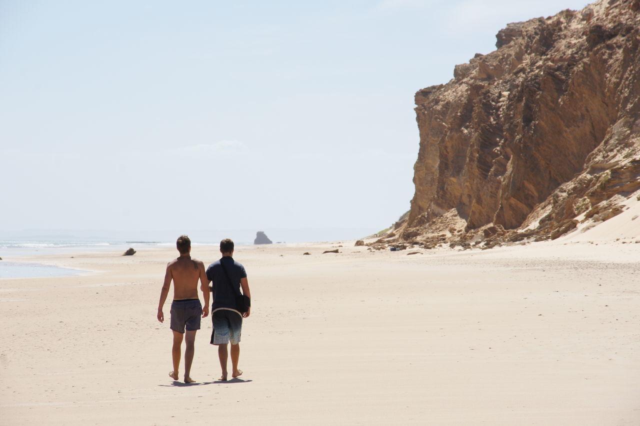 Rear View Of Men Walking On Beach