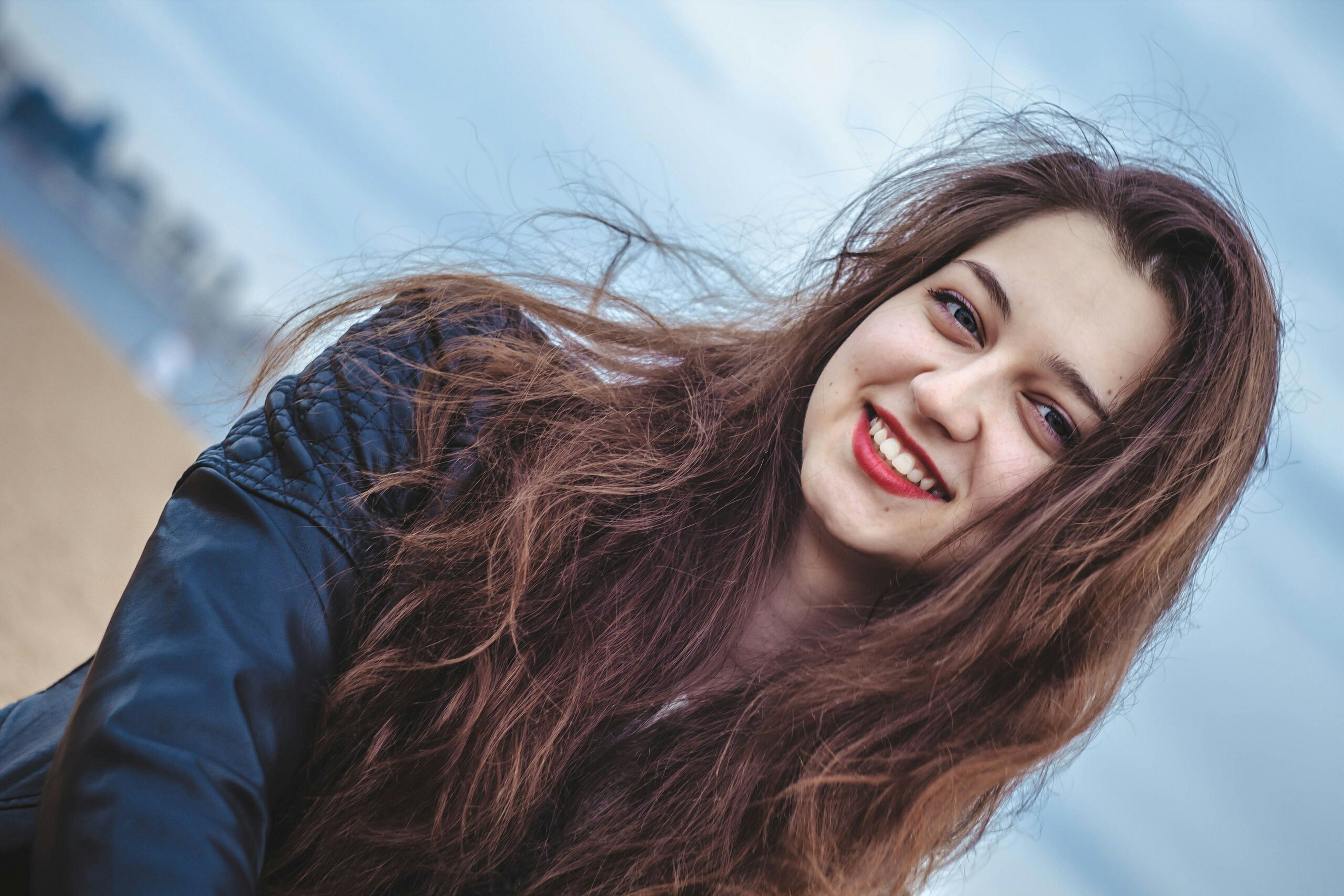 young adult, young women, person, long hair, lifestyles, portrait, looking at camera, leisure activity, headshot, front view, smiling, waist up, sky, casual clothing, brown hair, beauty, happiness