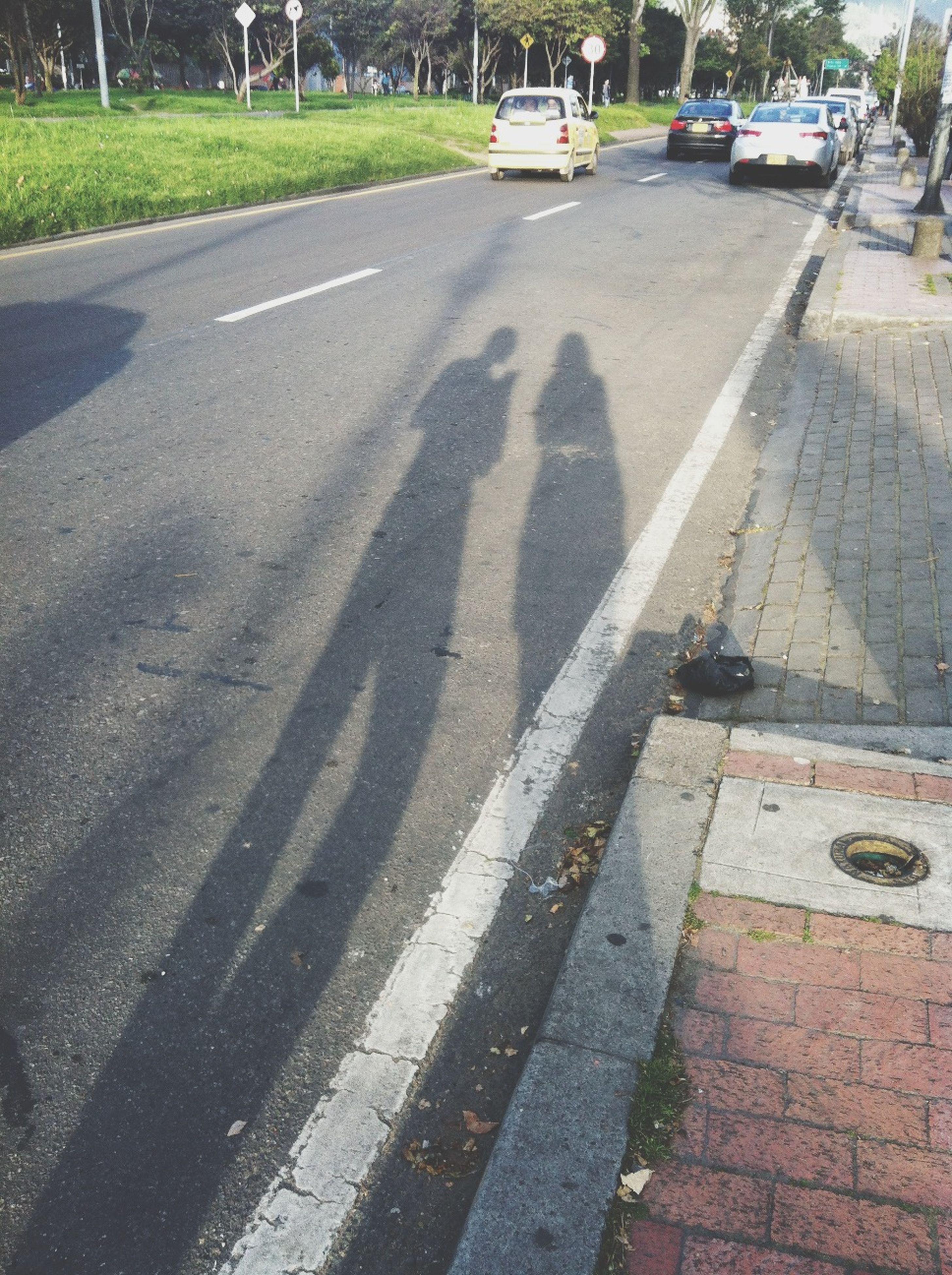 street, transportation, road, road marking, asphalt, shadow, car, land vehicle, high angle view, the way forward, sunlight, day, zebra crossing, city, outdoors, city street, city life, sidewalk, incidental people
