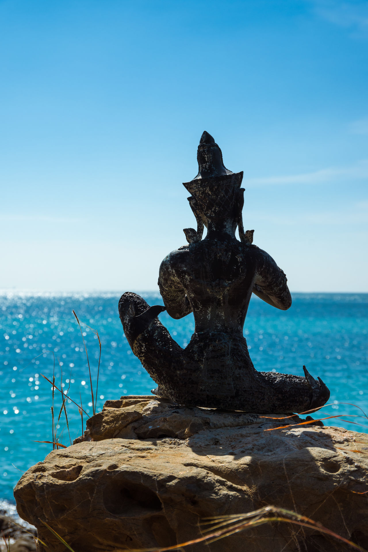 Seated Buddhist statue on a rock looking out to the ocean at Hat Nang Ram beach in Sattahip, Thailand Asian  Beach Buddha Buddhism Buddhist Day Horizon Over Water Meditation Outdoors Peace Peaceful Pray Rock Sculpture Sea Seated Sitting Sky Spirituality Statue Stone Thailand Tranquility Travel Water