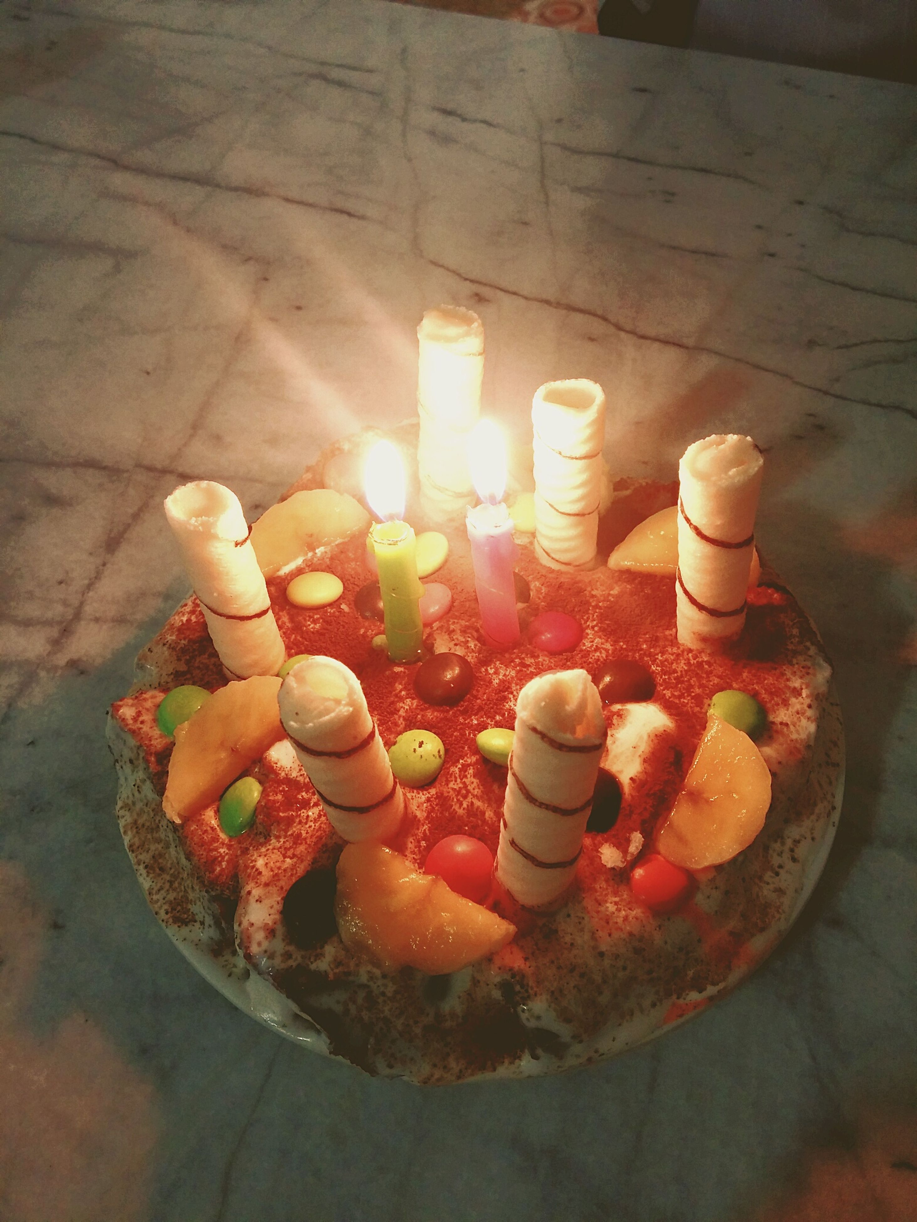 flame, burning, candle, indoors, fire - natural phenomenon, spirituality, religion, glowing, heat - temperature, sweet food, large group of objects, dessert, place of worship, temptation, candlelight, birthday candles, lit, tea light, multi colored, religious offering, unhealthy eating, freshness