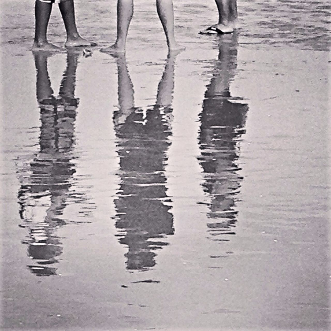 Reflection Of Three People On Beach