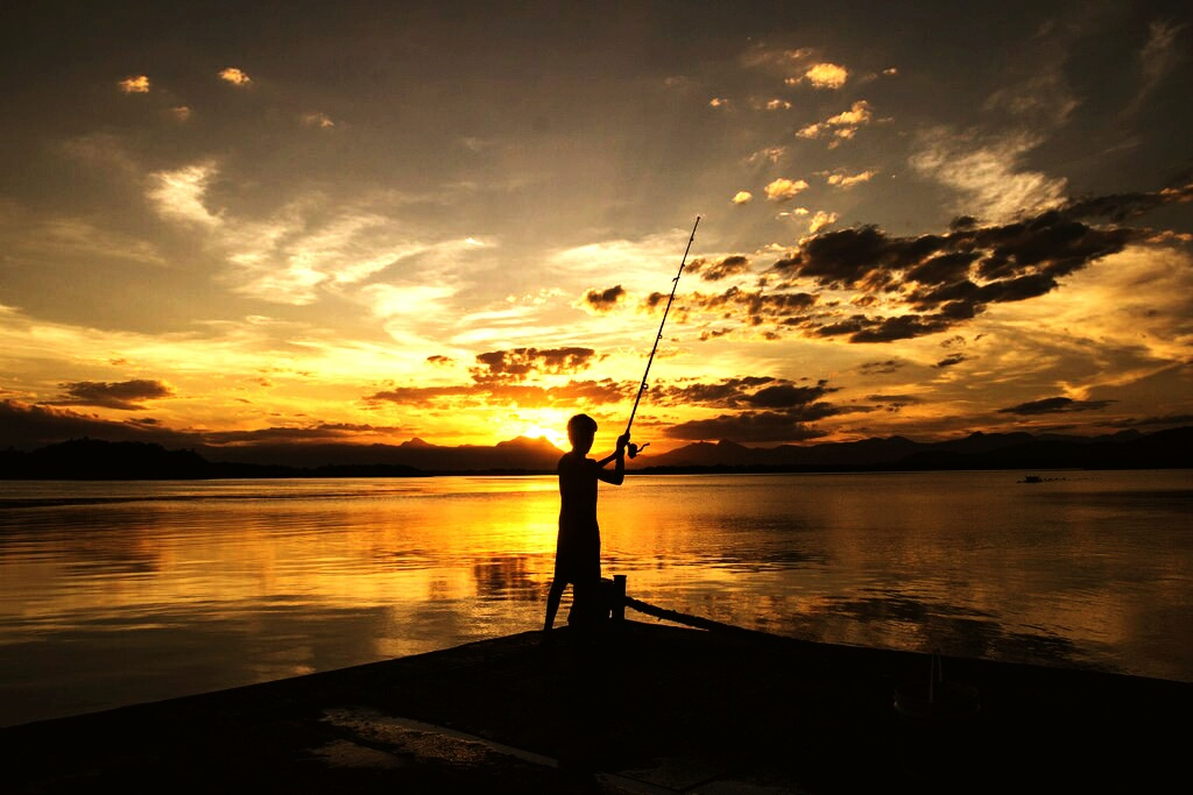 water, sunset, silhouette, sky, sea, lifestyles, leisure activity, scenics, tranquil scene, tranquility, beauty in nature, cloud - sky, reflection, horizon over water, men, full length, nature, standing