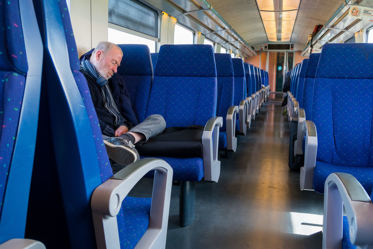 sitting, one person, mature adult, indoors, mature men, transportation, one mature man only, travel, one man only, men, vehicle seat, only men, full length, real people, day, adult, adults only, people