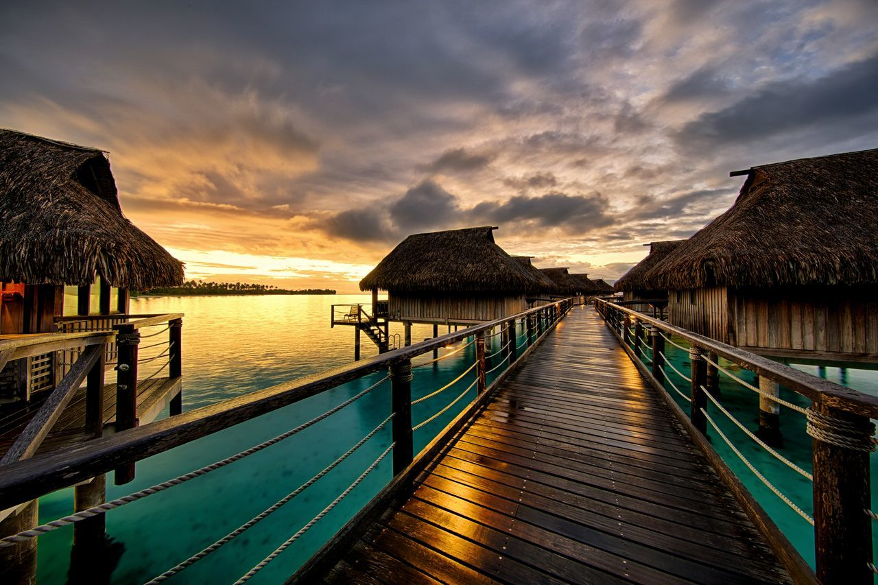 Pier And Stilt Houses Over Sea Against Cloudy Sky During Sunset