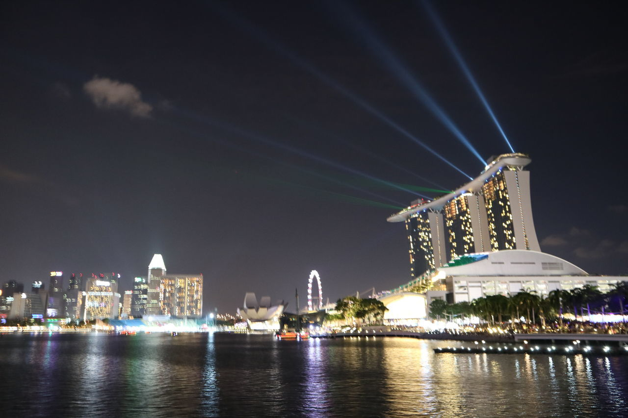 architecture, built structure, night, building exterior, illuminated, city, travel destinations, sky, skyscraper, tourism, waterfront, water, outdoors, cityscape, arts culture and entertainment, urban skyline, modern, no people