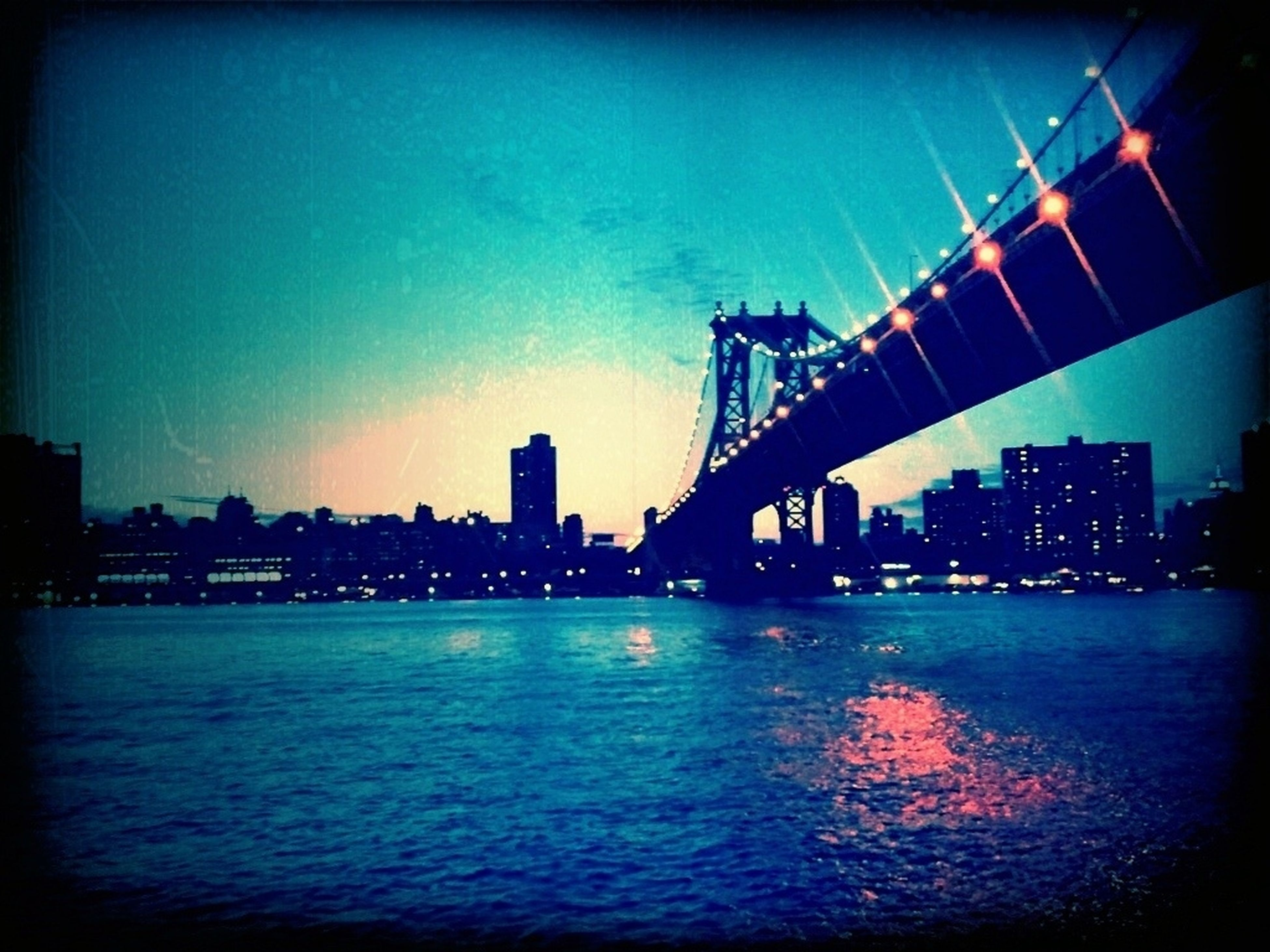architecture, built structure, water, waterfront, building exterior, city, illuminated, river, transfer print, sunset, blue, connection, clear sky, bridge - man made structure, sky, reflection, auto post production filter, dusk, sea, silhouette