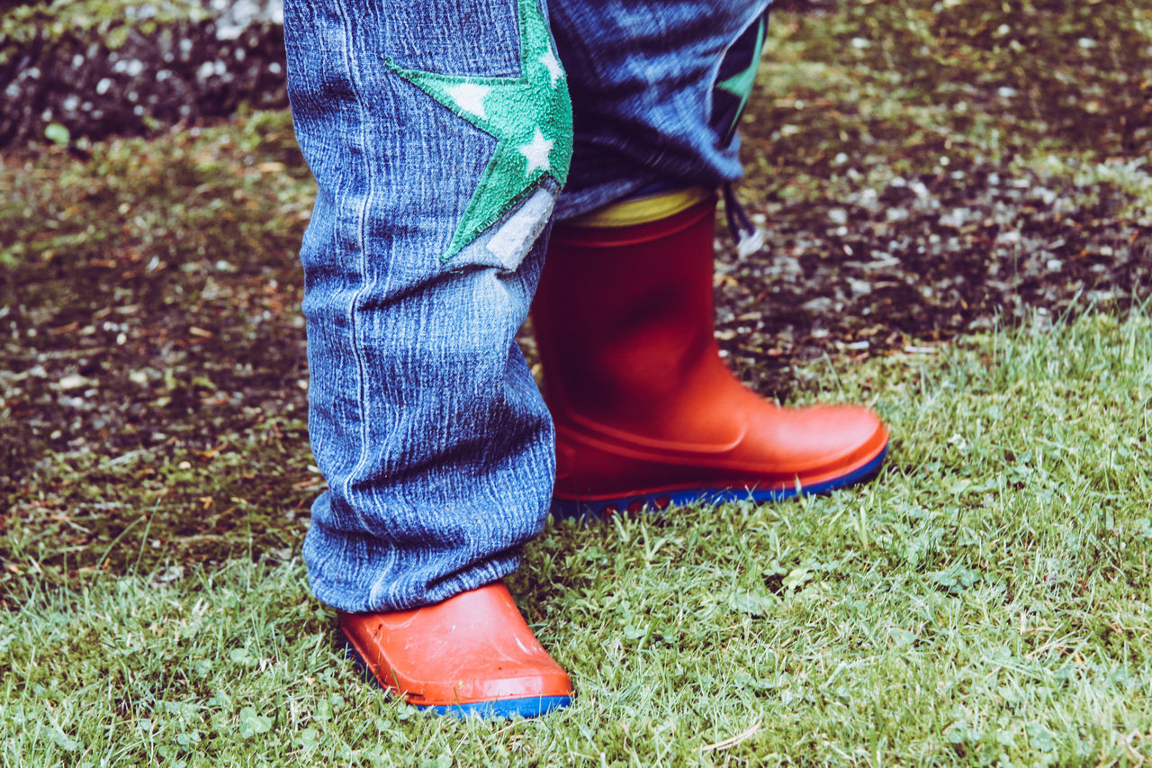 Blue Boy Child Childhood Close-up Day Grass Green Human Body Part Human Leg Jeans Little Boy Low Section One Person Outdoors Patches Real People Red Rubber Boots Standing Star These Boots Are Made For Walking