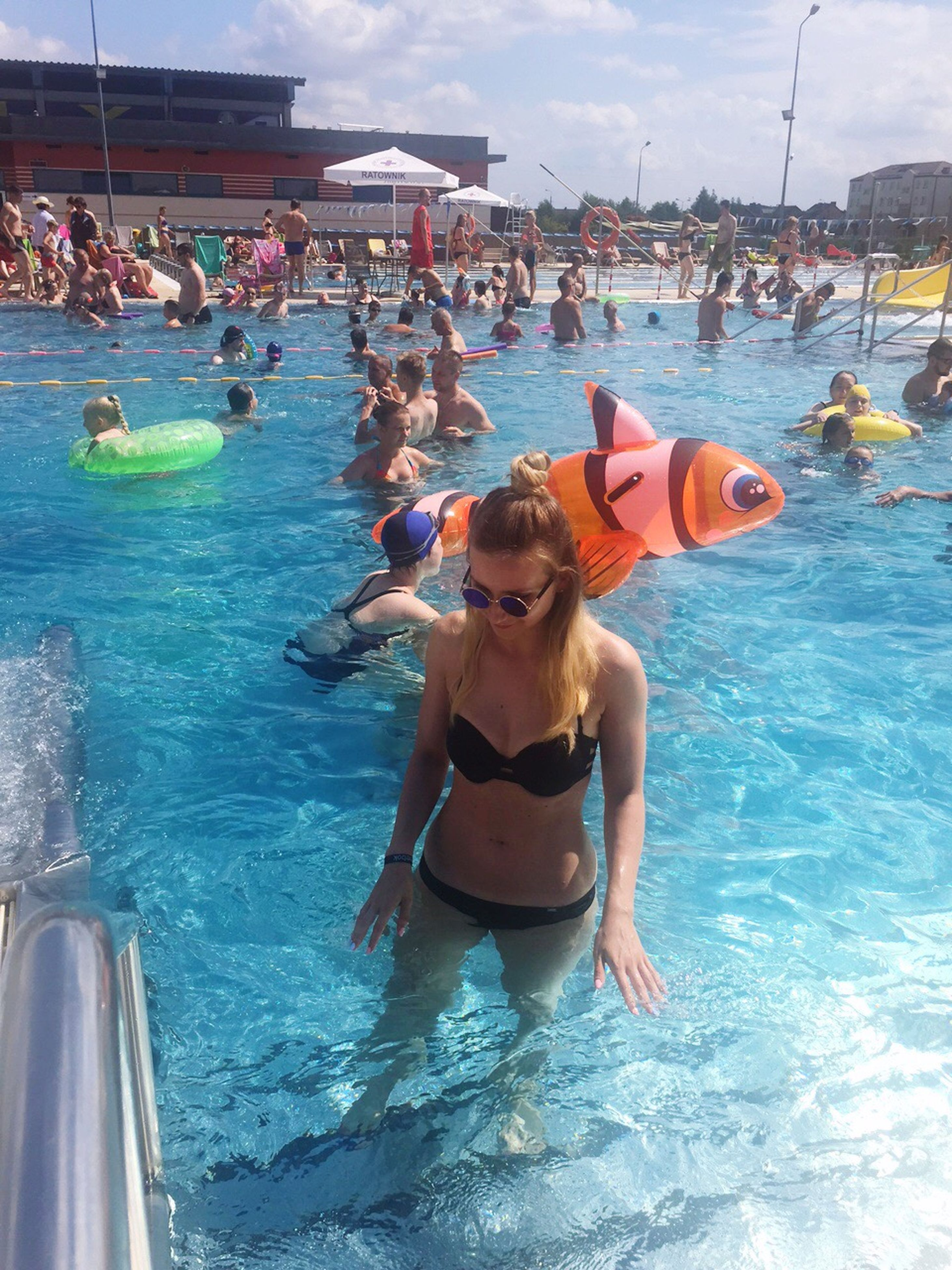 water, swimming pool, real people, leisure activity, enjoyment, lifestyles, fun, day, outdoors, full length, shirtless, large group of people, happiness, vacations, men, swimming, smiling, young adult, people