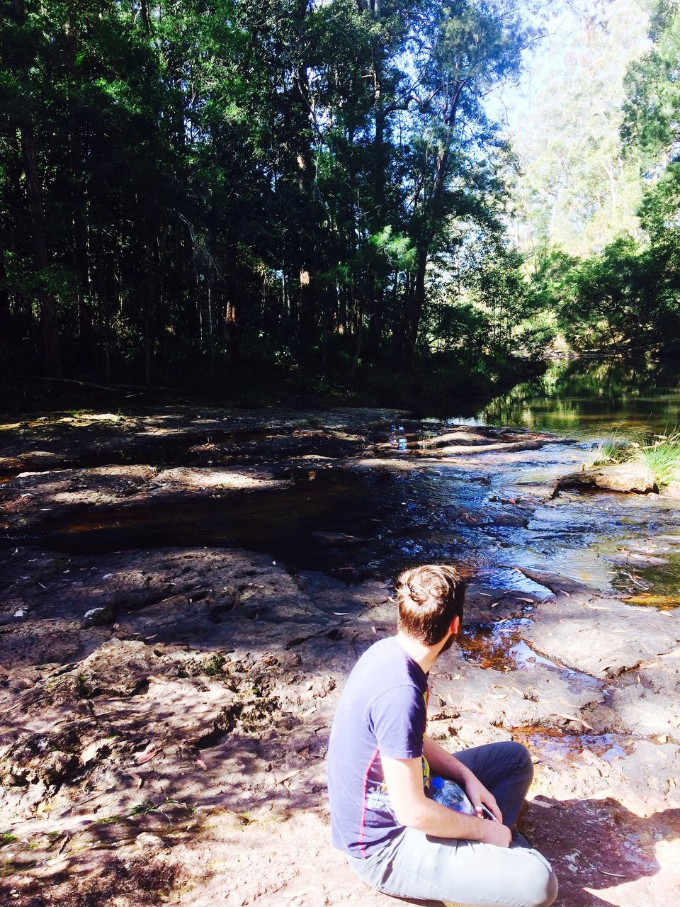 Side View Of Man Sitting At Riverbank In Forest
