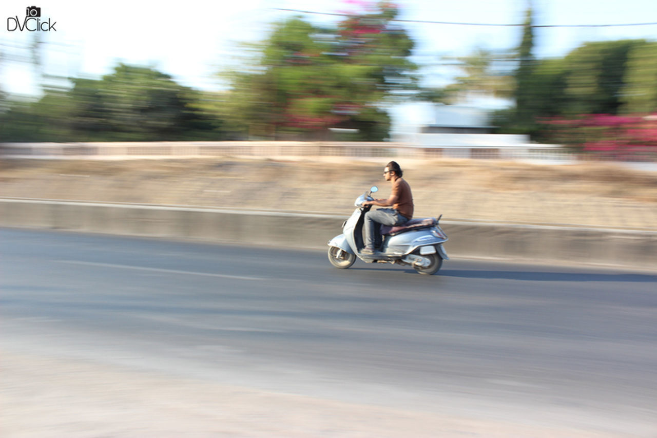 transportation, motorcycle, blurred motion, riding, mode of transport, speed, motion, land vehicle, real people, road, day, one person, full length, sitting, outdoors, men, lifestyles, helmet, biker, adventure, nature, headwear, sky, people