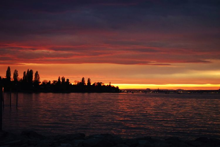 Sunset Sky Silhouette Beauty In Nature Water Nature Dramatic Sky Cloud - Sky Scenics Tranquility No People Tranquil Scene River Outdoors Architecture Building Exterior City Tree Cityscape Bodensee Bodensee Konstanz Bodenseebilder Bodensee Lake Altnau