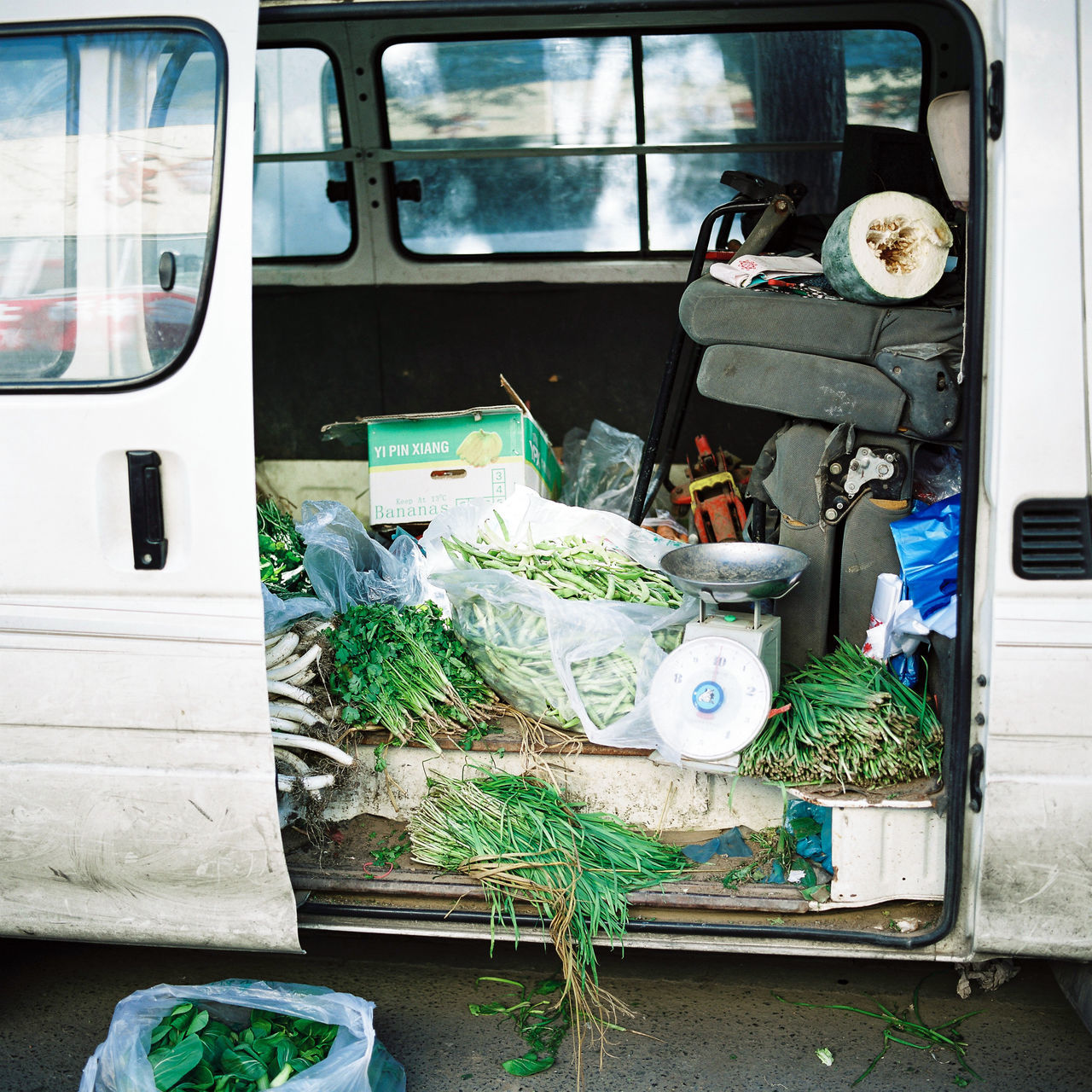A vendor's van and his goods alongside a market stall in the Chinese capital of Beijing. Bananas Beijing Car China City Film Food Goods Land Vehicle Market Messy No People Outdoor Market Outdoors Peas Scale  Street Photography Transportation Travel Unhygienic Unsanitary Van Vegetables Vendor