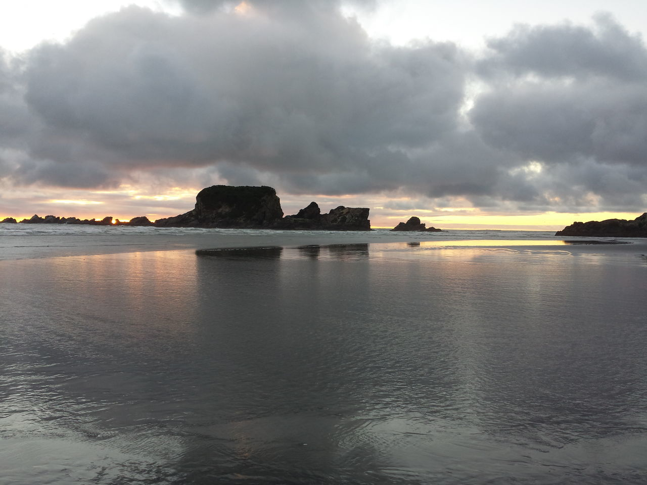Scenic View Of Shore Against Cloudy Sky During Sunset