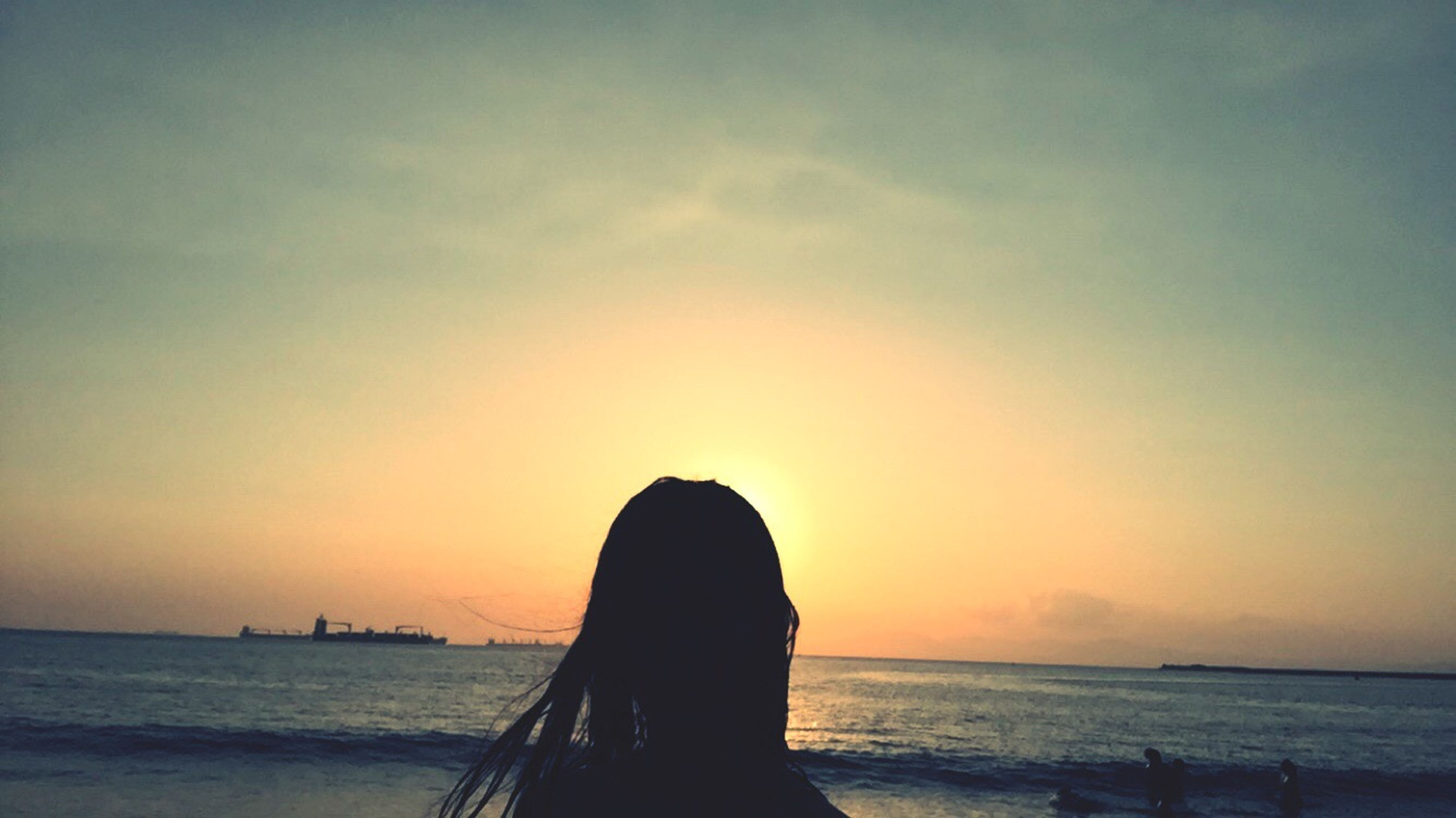 sea, water, horizon over water, sunset, scenics, silhouette, sky, tranquility, beauty in nature, tranquil scene, beach, orange color, idyllic, nature, standing, shore, person, lifestyles