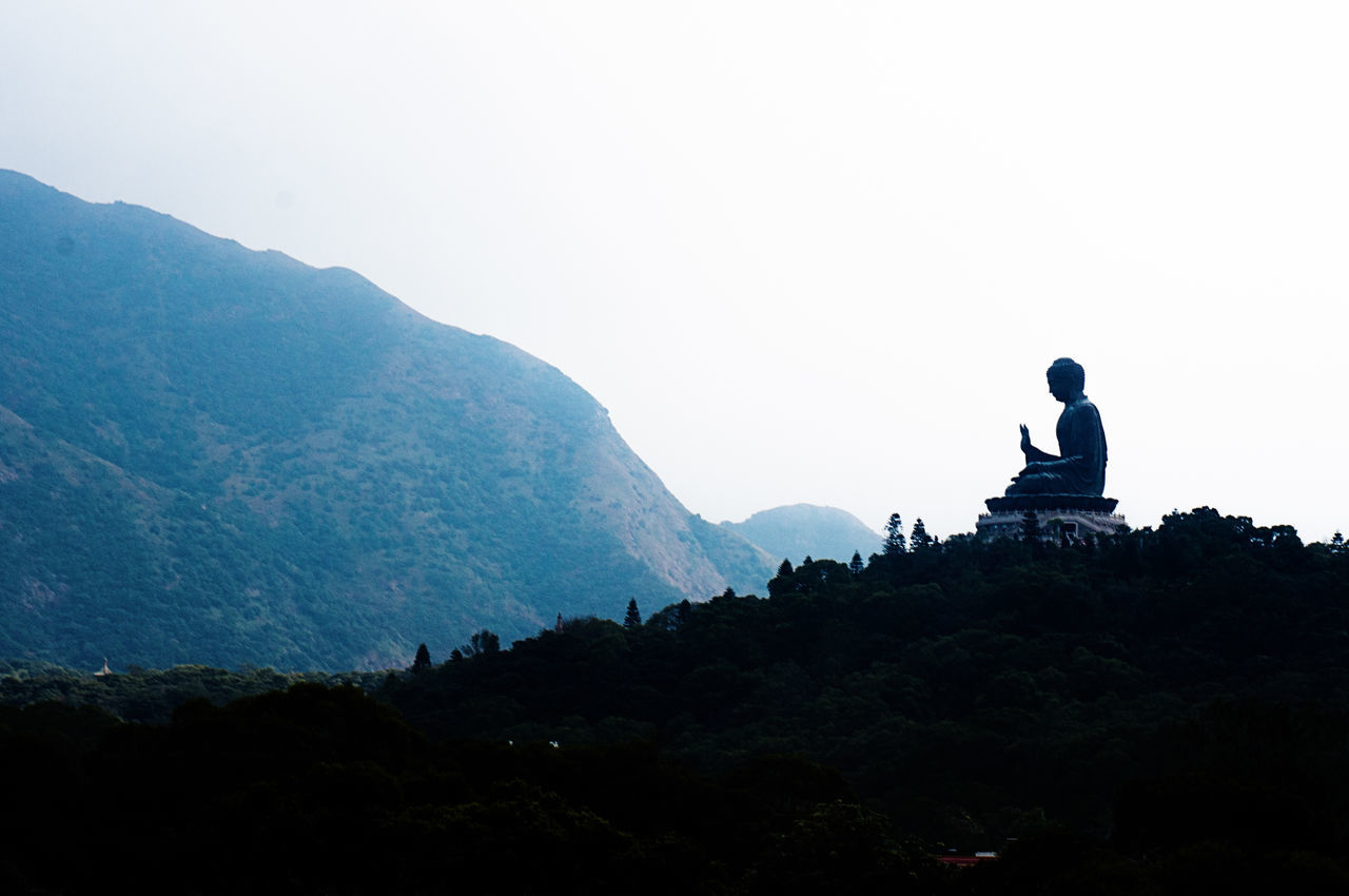 Low Angle View Of Buddha Statue On Mountain Against Clear Sky