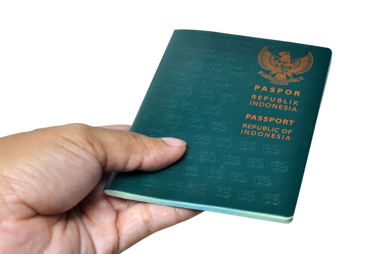 Cropped Hand Holding Passport Against White Background