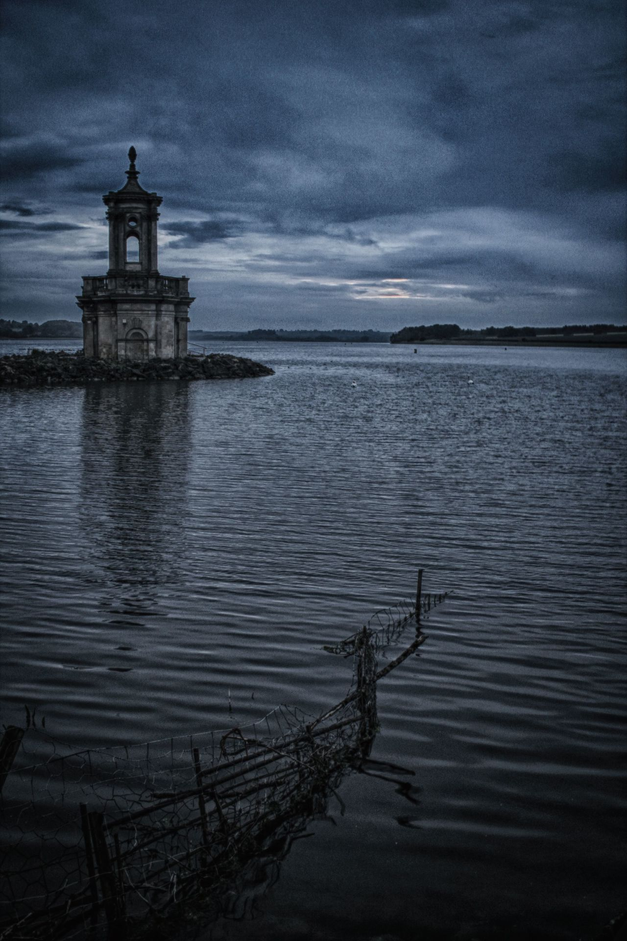 Lone church on water edge at dusk with a fence leading into the lake. Beauty In Nature Church Cloud - Sky Fence In A Lake Lake At Night Lakeshore Nature No People Non-urban Scene Outdoors Sky Water Water Edge Water Reflection