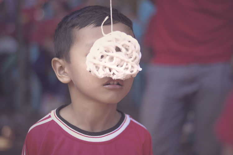 Lomba Makan Kerupuk Boys Casual Clothing Child Childhood Close-up Day Elementary Age Focus On Foreground Headshot Leisure Activity Lifestyles One Boy Only One Person Outdoors People Real People