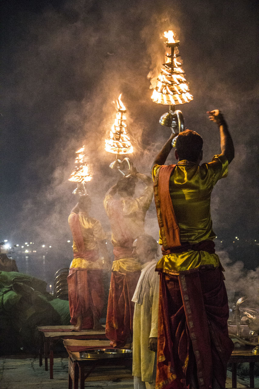 night, real people, celebration, men, standing, rear view, traditional festival, religion, outdoors, sky, firework display, illuminated, firework - man made object, lifestyles, large group of people, architecture, people