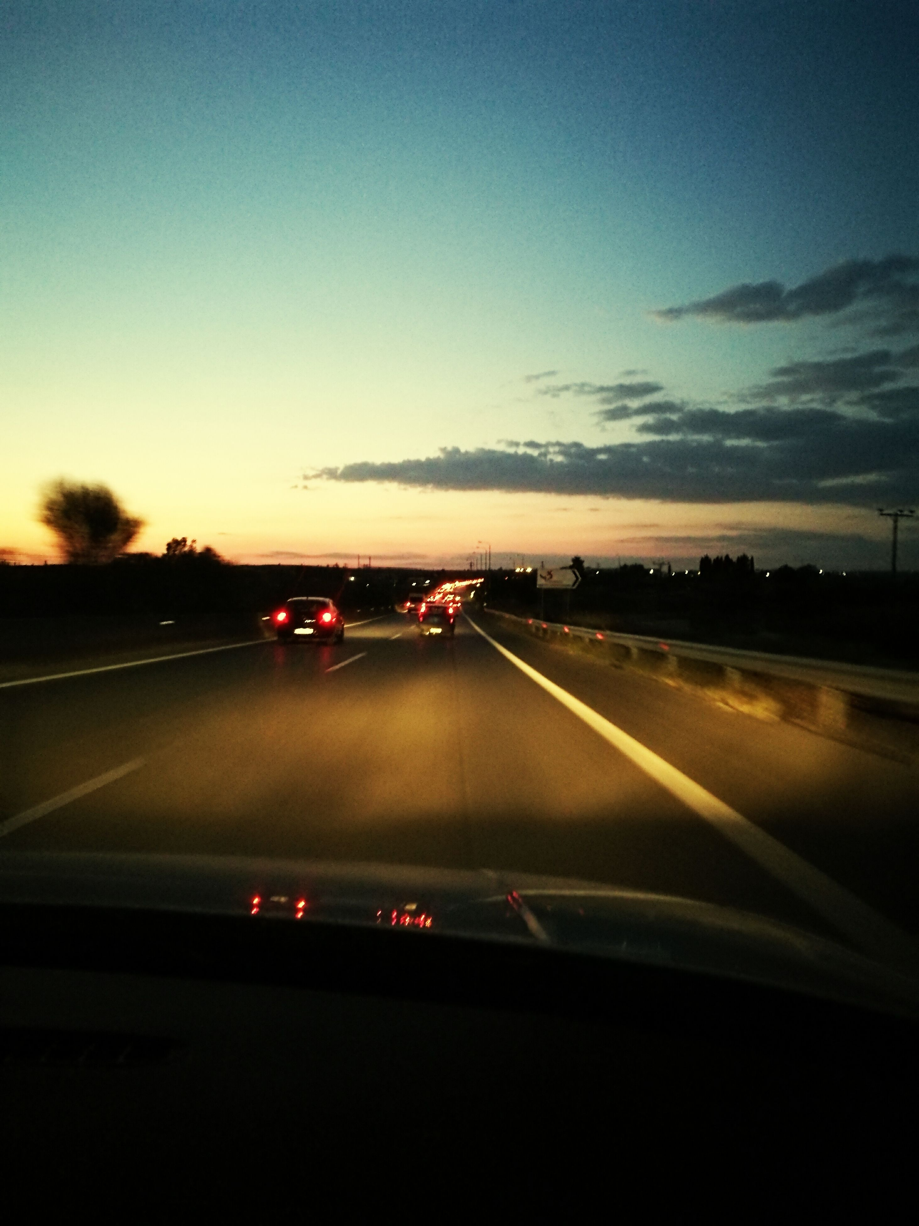 transportation, car, land vehicle, mode of transport, road, on the move, sunset, sky, car interior, road marking, motion, illuminated, dusk, the way forward, diminishing perspective, orange color, cloud - sky, car point of view, cloud, dividing line, outdoors, journey, nature, long, vanishing point, tail light