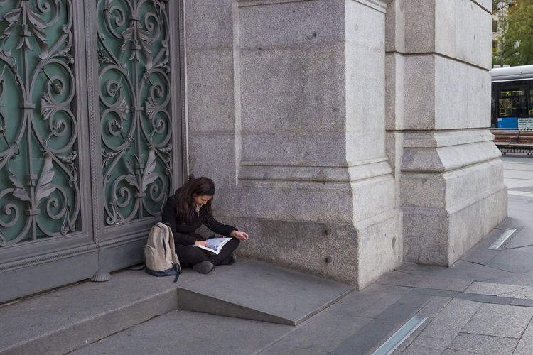 A young woman sitting in the doorway of the Bank of Spain reading a book in Madrid. City City Life City Street Reading Architectural Column Architecture Book Built Structure Corner Day Door Way Doorway Editorial  Lifestyles Long Hair One Person Outdoors People Real People Sitting Steps University Student Women Young Adult Young Women
