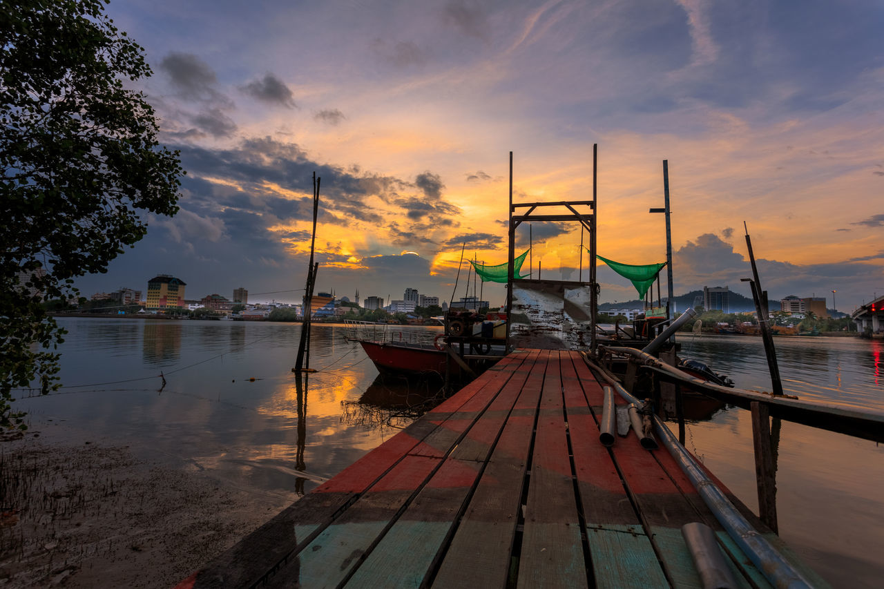 sunset, water, sky, nautical vessel, cloud - sky, transportation, orange color, nature, mode of transport, reflection, moored, outdoors, beauty in nature, scenics, wood - material, no people, sea, jetty, tree, longtail boat, day