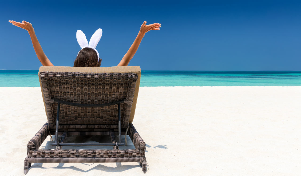 Woman with bunny ears in a sunchair at a tropical beach Beach Blue Bunny  Concept Ears Easter Hands Happy Holiday Lifestyles Maldives One Person Rear View Relaxation Sand Sea Sky Summer Sunchair Tropics Vacation Vacations Water