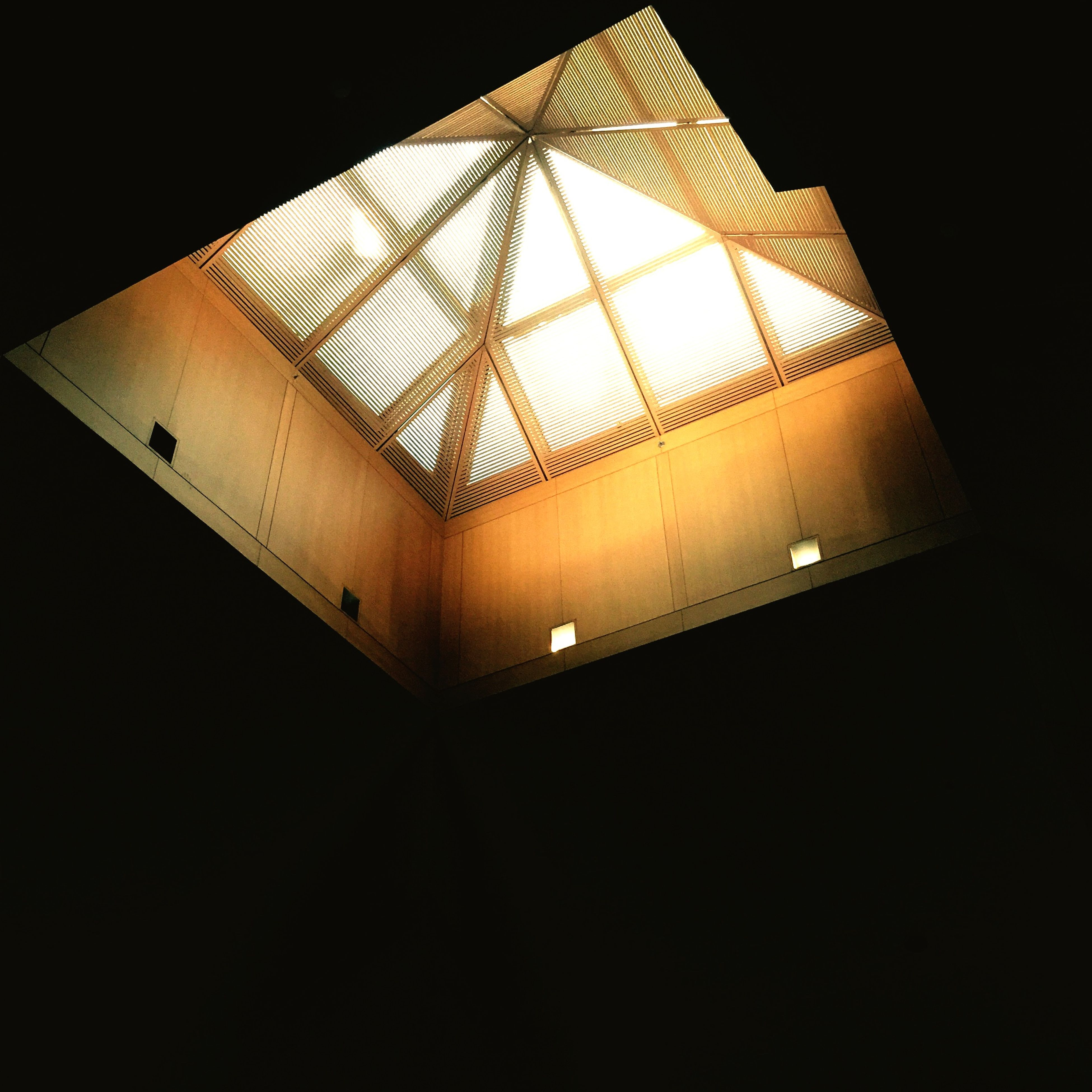 indoors, low angle view, architecture, built structure, ceiling, modern, building, staircase, illuminated, wall - building feature, no people, sunlight, shadow, lighting equipment, steps and staircases, directly below, window, steps, pattern, home interior