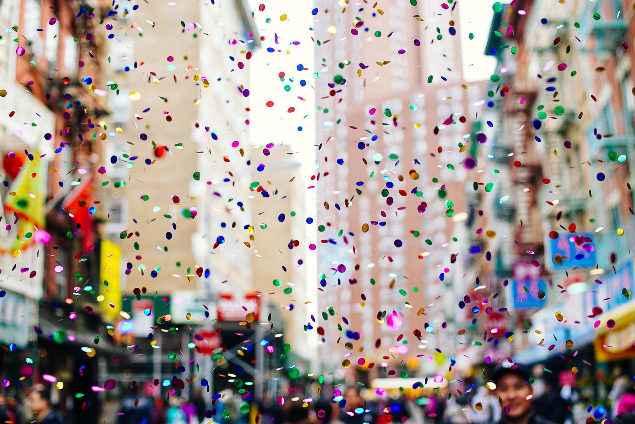 Confetti fills the air during the Chinese New Year celebration in Chinatown, New York City. Chinatown Chinatown, Singapore New year Celebration chinese new year close-up confetti day enjoyment Fun indoors large group of people multi colored new year celebration