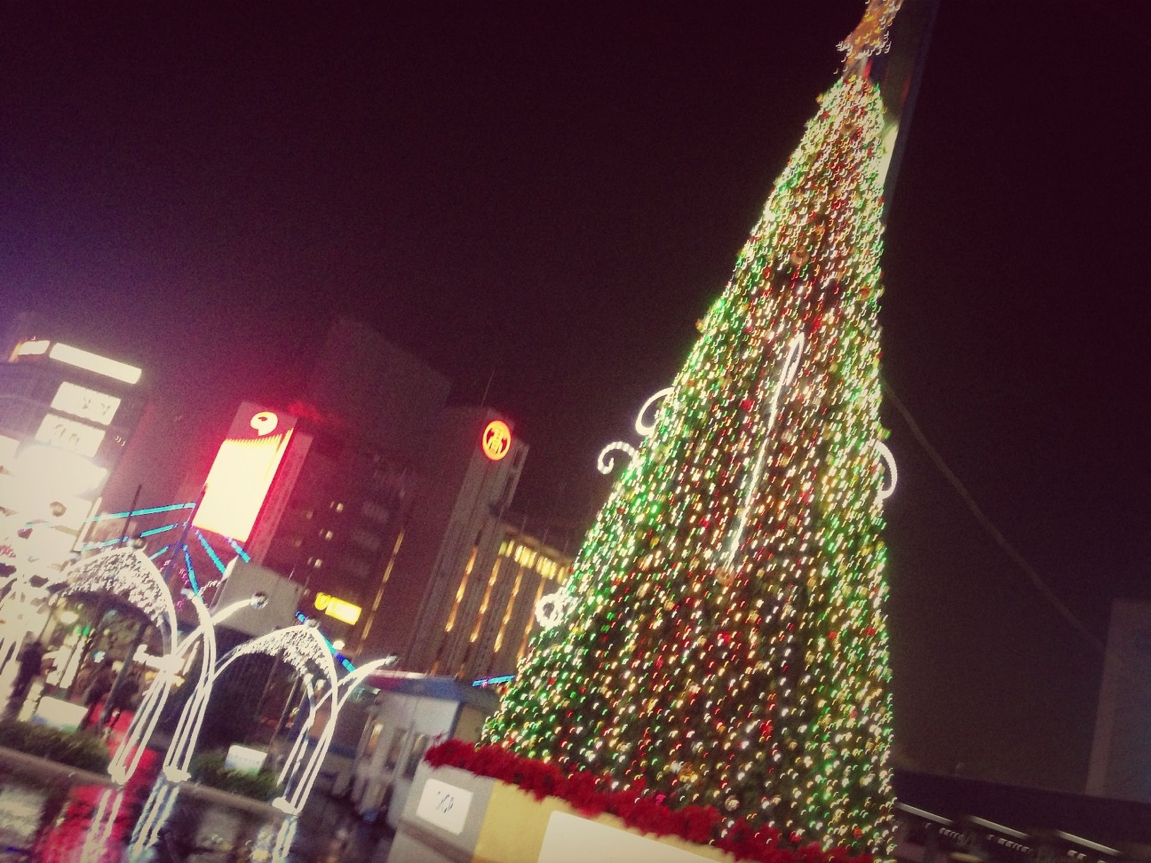 illuminated, architecture, building exterior, night, built structure, city, low angle view, decoration, lighting equipment, clear sky, building, no people, residential building, outdoors, hanging, multi colored, christmas, residential structure, celebration, city life