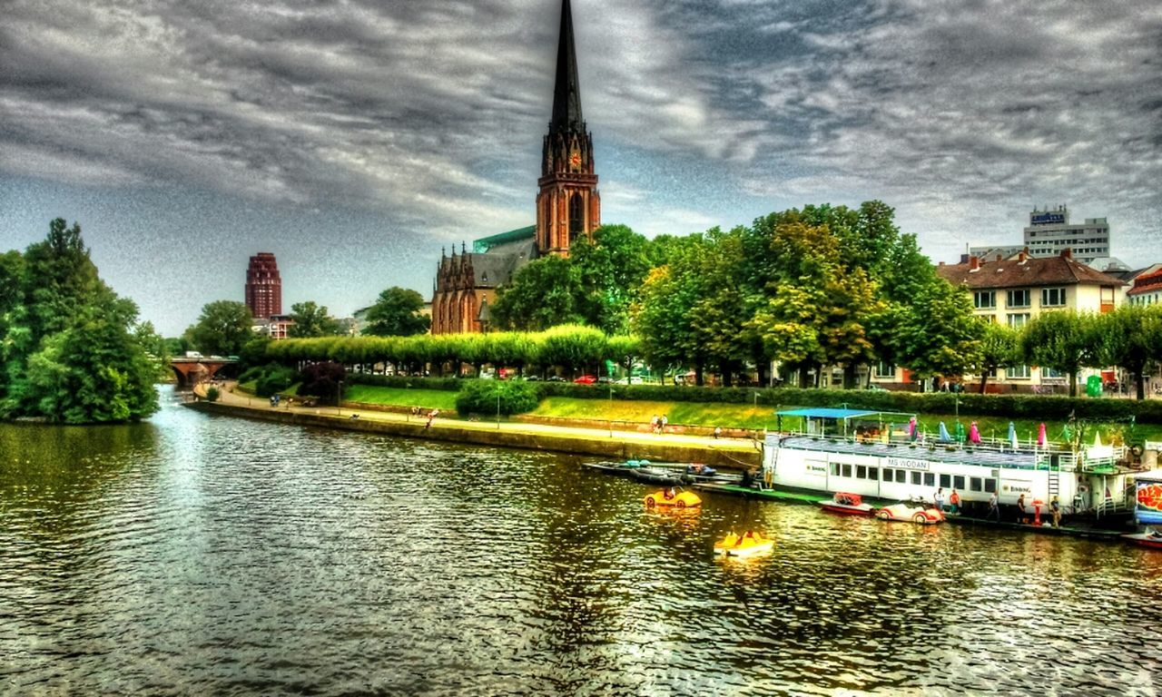 architecture, building exterior, built structure, religion, church, tree, water, waterfront, tower, river, spirituality, place of worship, sky, cloud - sky, clock tower, overcast, cloudy, tall - high, outdoors, tall, steeple, in front of, spire, tourism, cloudscape