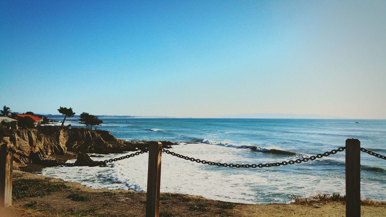 sea, beach, horizon over water, water, clear sky, scenics, sand, beauty in nature, tranquil scene, nature, railing, shore, copy space, blue, tranquility, outdoors, day, vacations, no people, travel destinations, wave, sky