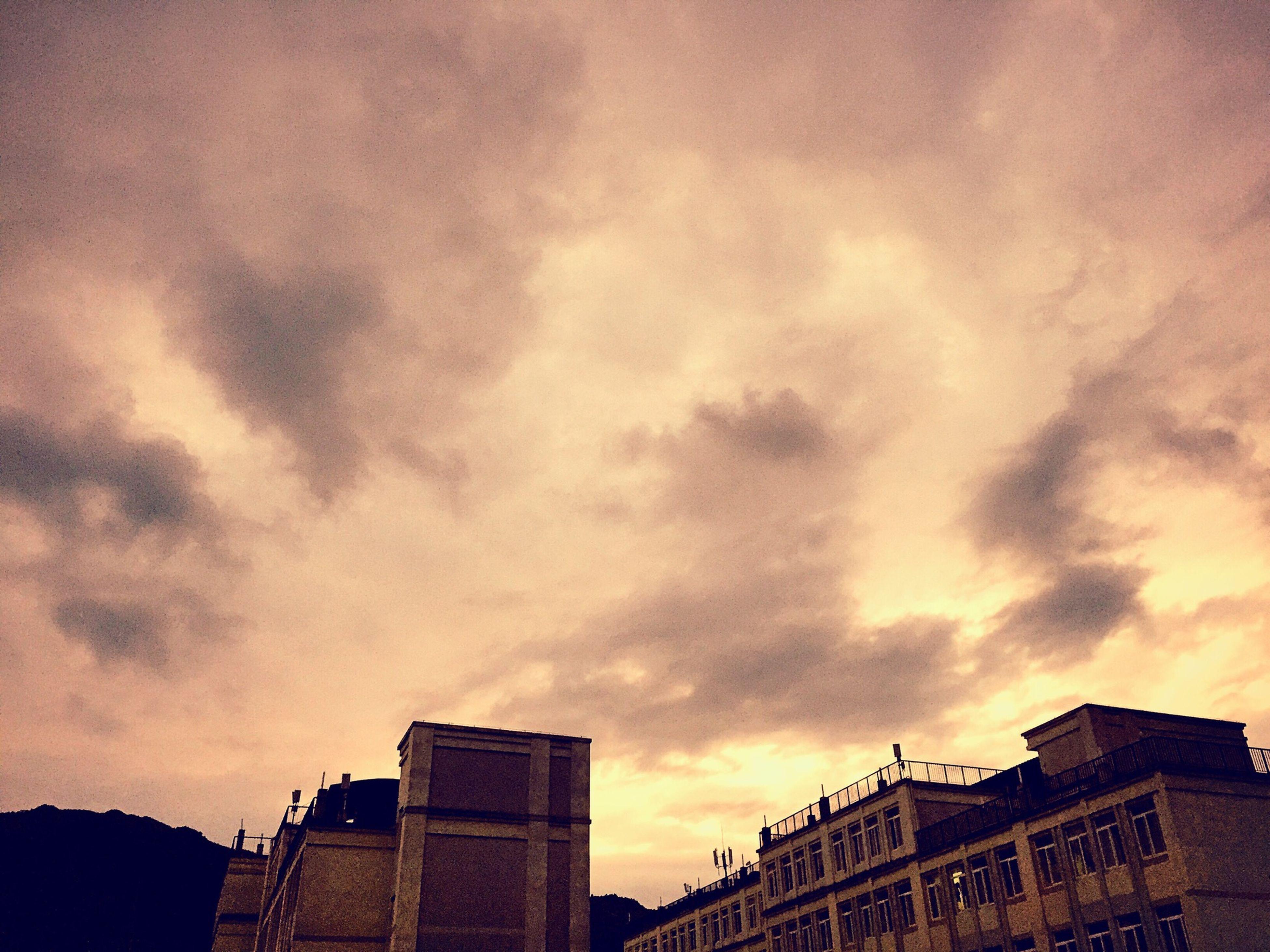 architecture, building exterior, built structure, low angle view, sky, cloud - sky, sunset, cloudy, silhouette, building, city, cloud, high section, overcast, residential building, residential structure, outdoors, weather, orange color, dusk
