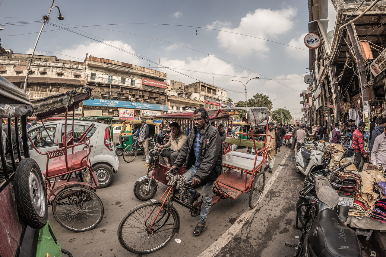transportation, mode of transport, bicycle, land vehicle, stationary, building exterior, street, outdoors, architecture, built structure, day, city, real people, motorcycle, large group of people, sky, road, men, people