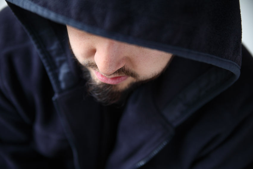 Man in hooded jacket looks down Bearded Black Black Color Black Hoodie Copy Space Dark Jacket Depressed Indoors  Lonely Looking Down Man Millenial Mustache Natural Light Pensive Mood Sad Serious Expression Thoughtful Warm Clothing