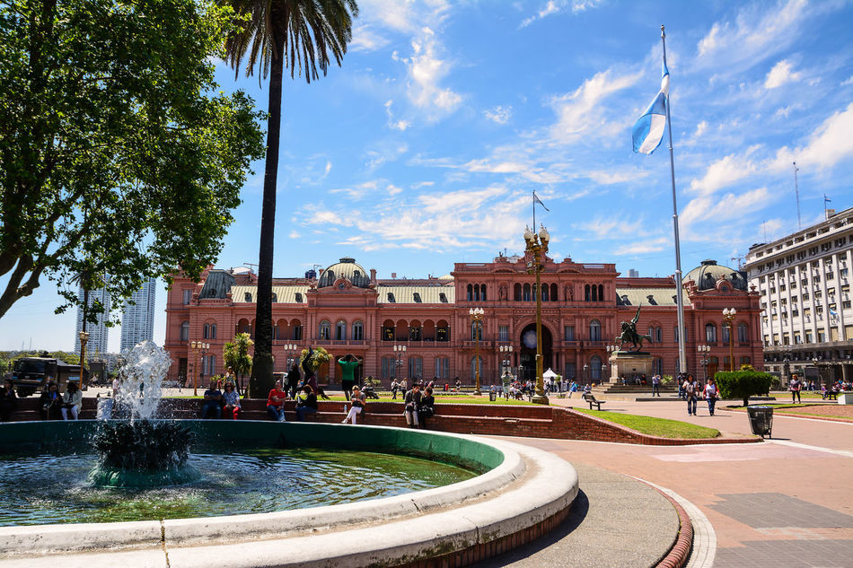 Buenos Aires, Argentina - Otober 30, 2016: Casa Rosada in Plaza de Mayo in Buenos aires with tourist in a sunny day. America Argentina Argentine Buenos Aires Building Capital Casa Rosada City Ciudad Autónoma De Buenos Aires Flag Fountain Government History House Landmark Palace People Pink Plaza De Mayo President Presidential Sightseeing Square Street Tourist