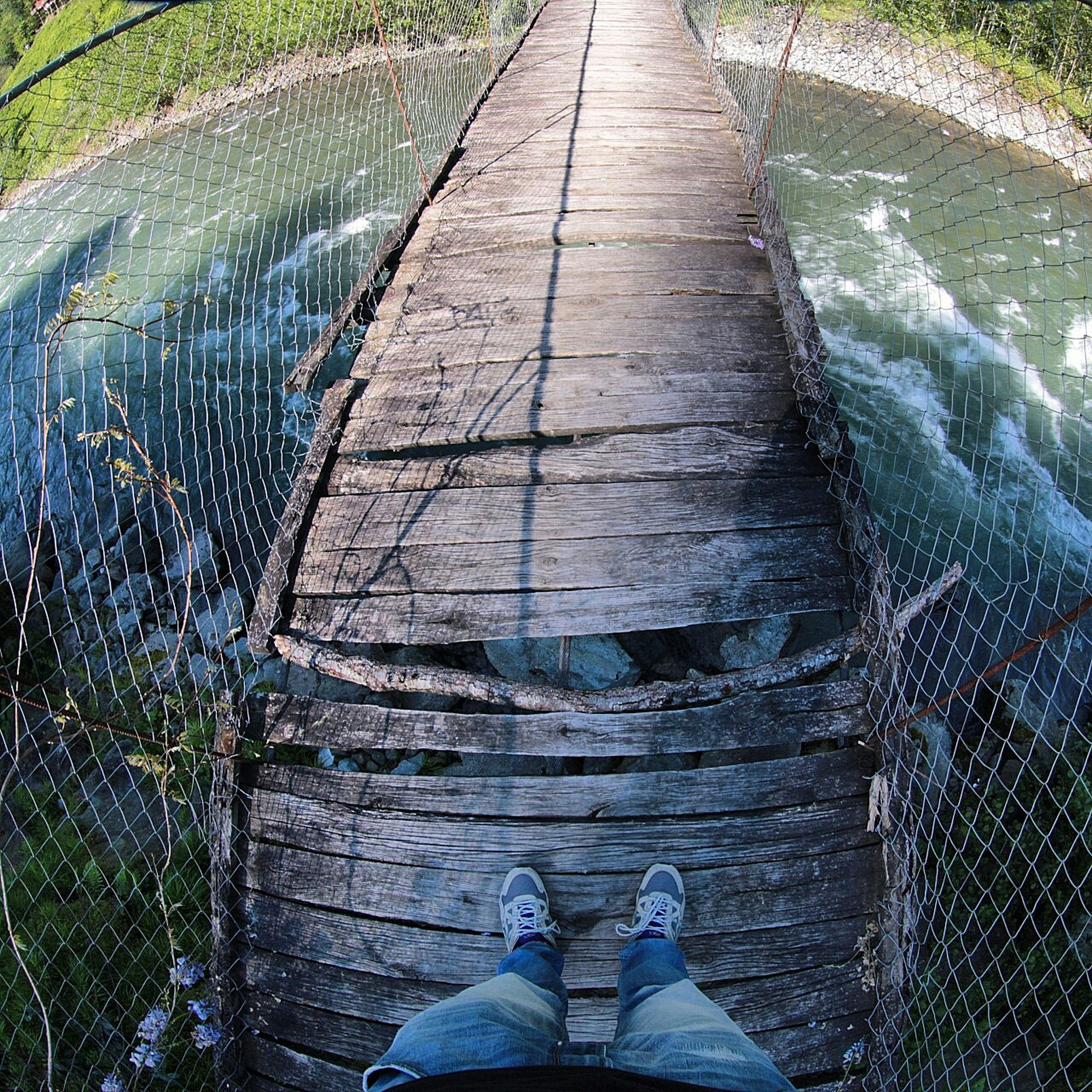 low section, water, person, high angle view, personal perspective, the way forward, shoe, lifestyles, men, human foot, standing, unrecognizable person, leisure activity, diminishing perspective, pier, day, boardwalk