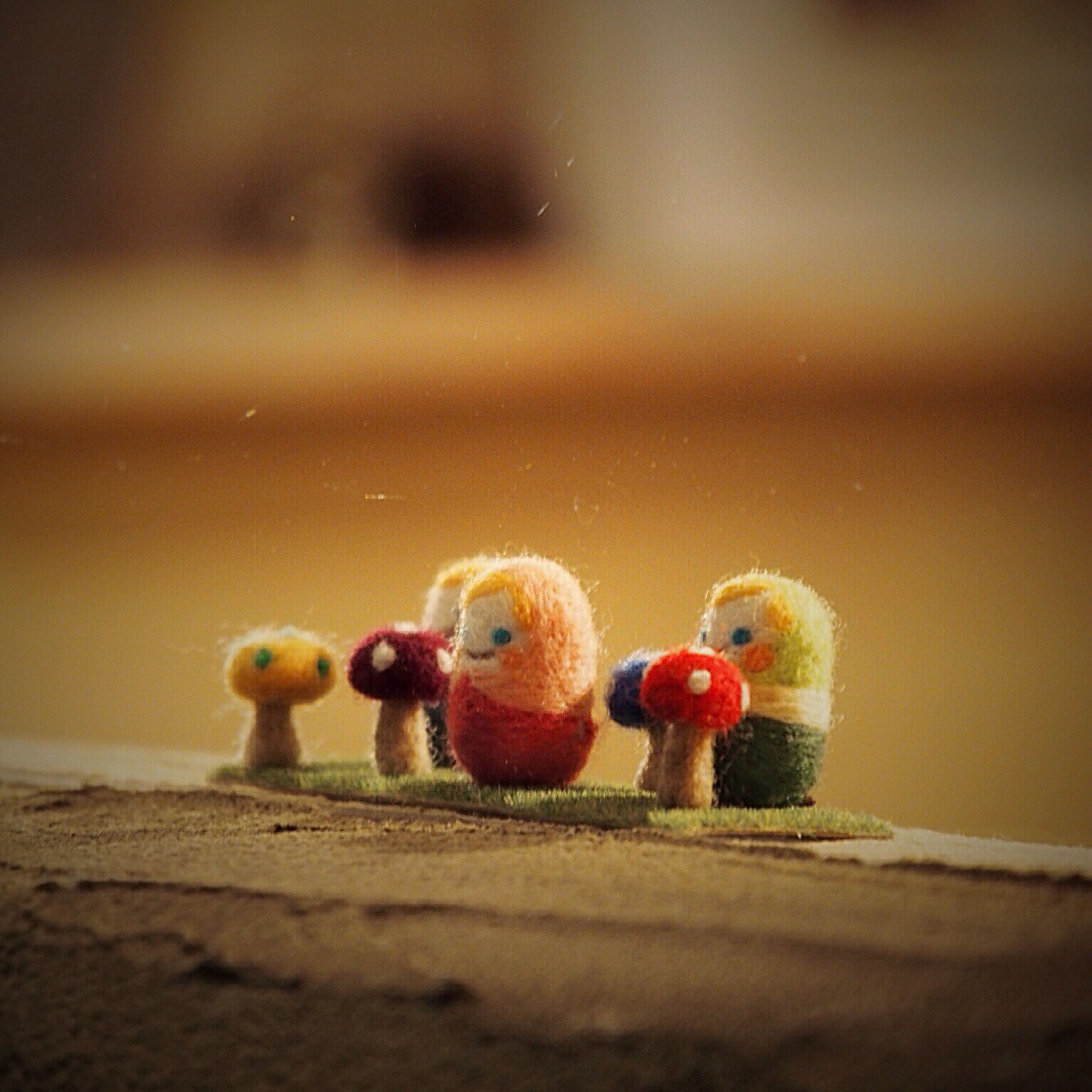 toy, childhood, selective focus, focus on foreground, animal themes, multi colored, close-up, animal representation, bird, day, outdoors, no people, two animals, full length, red, still life, nature, playful, wall - building feature