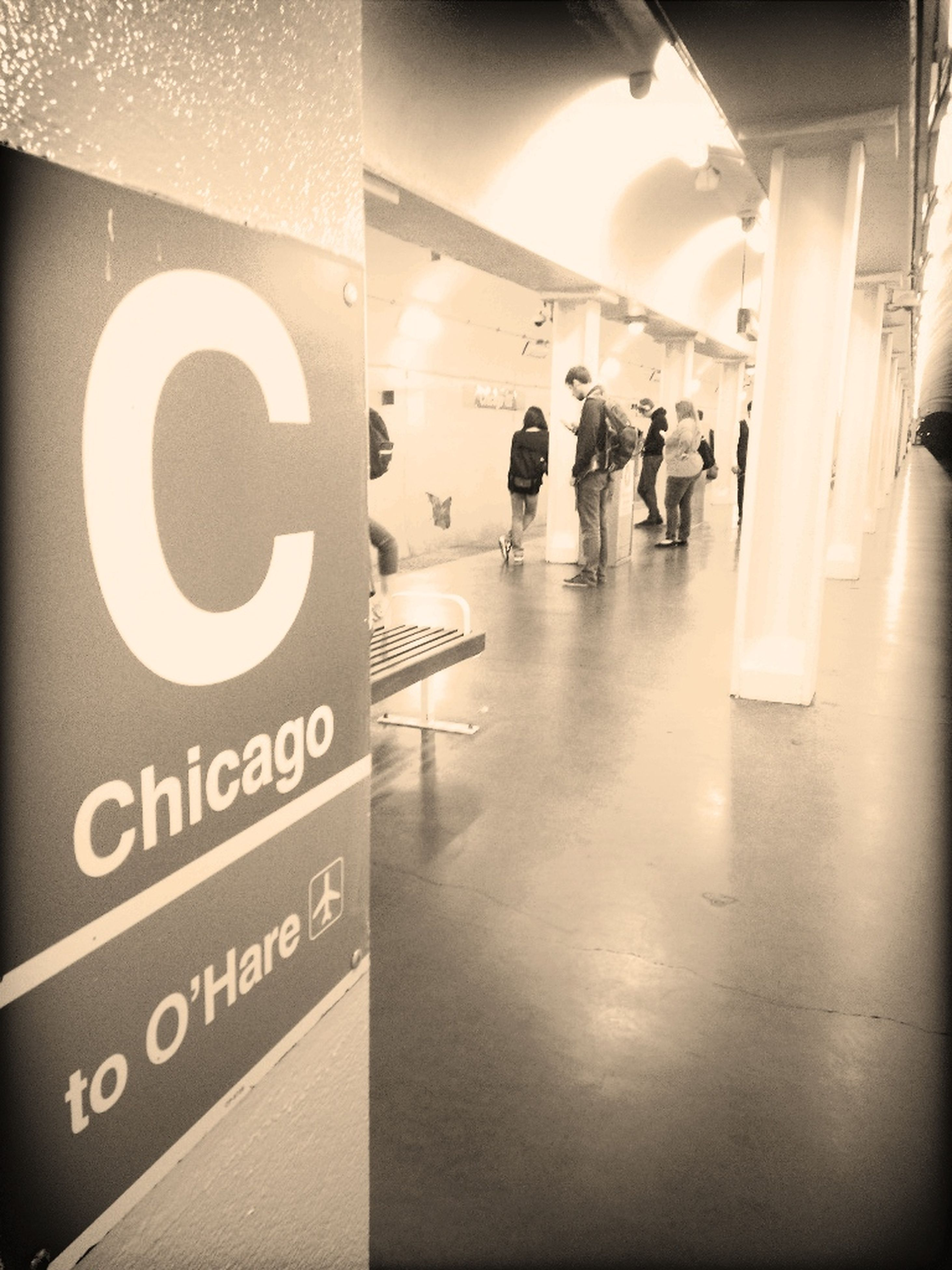 indoors, text, communication, western script, illuminated, information sign, built structure, architecture, sign, non-western script, subway station, number, guidance, arrow symbol, transportation, wall - building feature, reflection, capital letter, information, incidental people