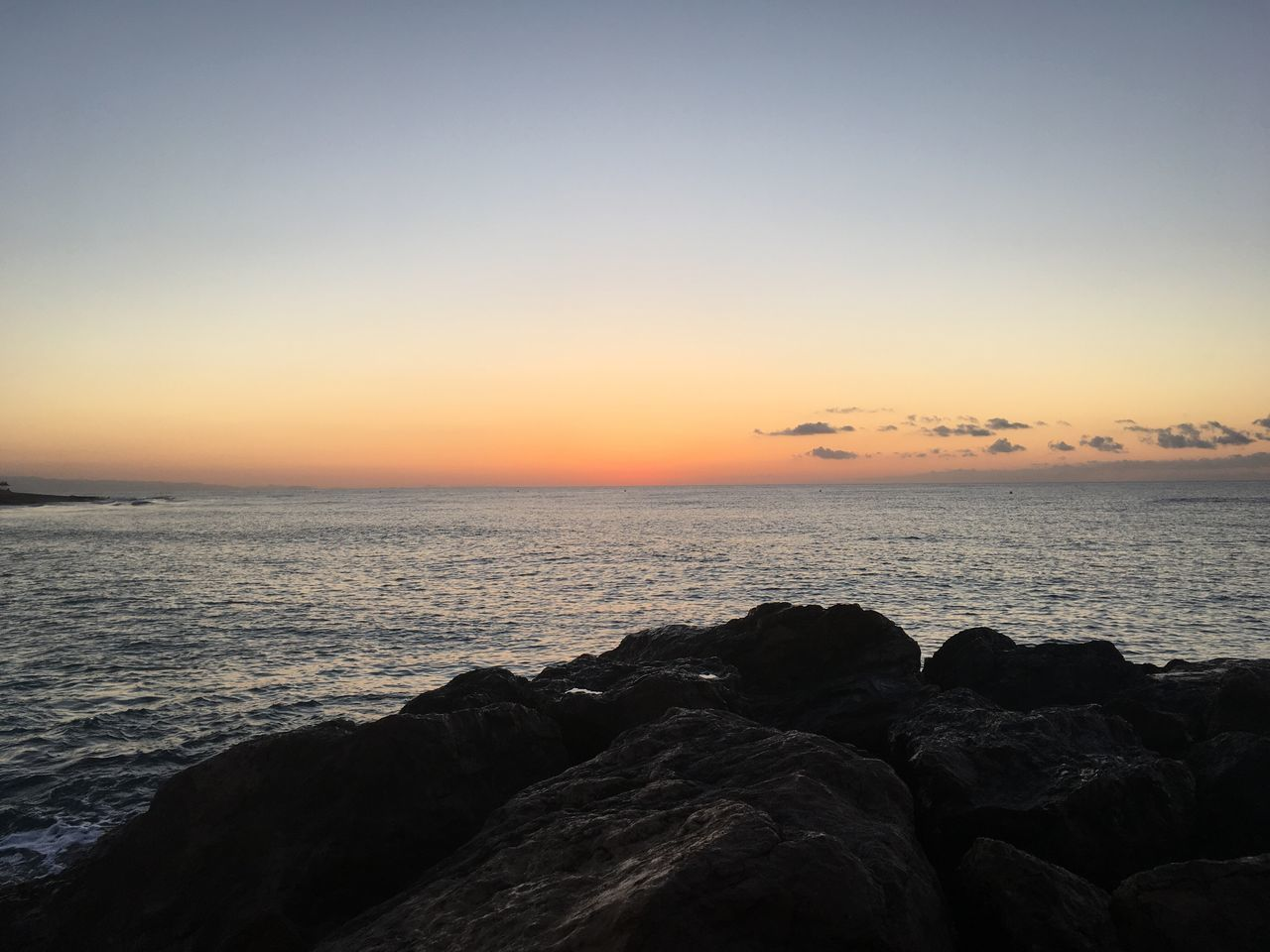 sea, sunset, horizon over water, beauty in nature, scenics, tranquil scene, nature, water, tranquility, idyllic, rock - object, beach, sky, outdoors, silhouette, no people, clear sky, pebble beach, day