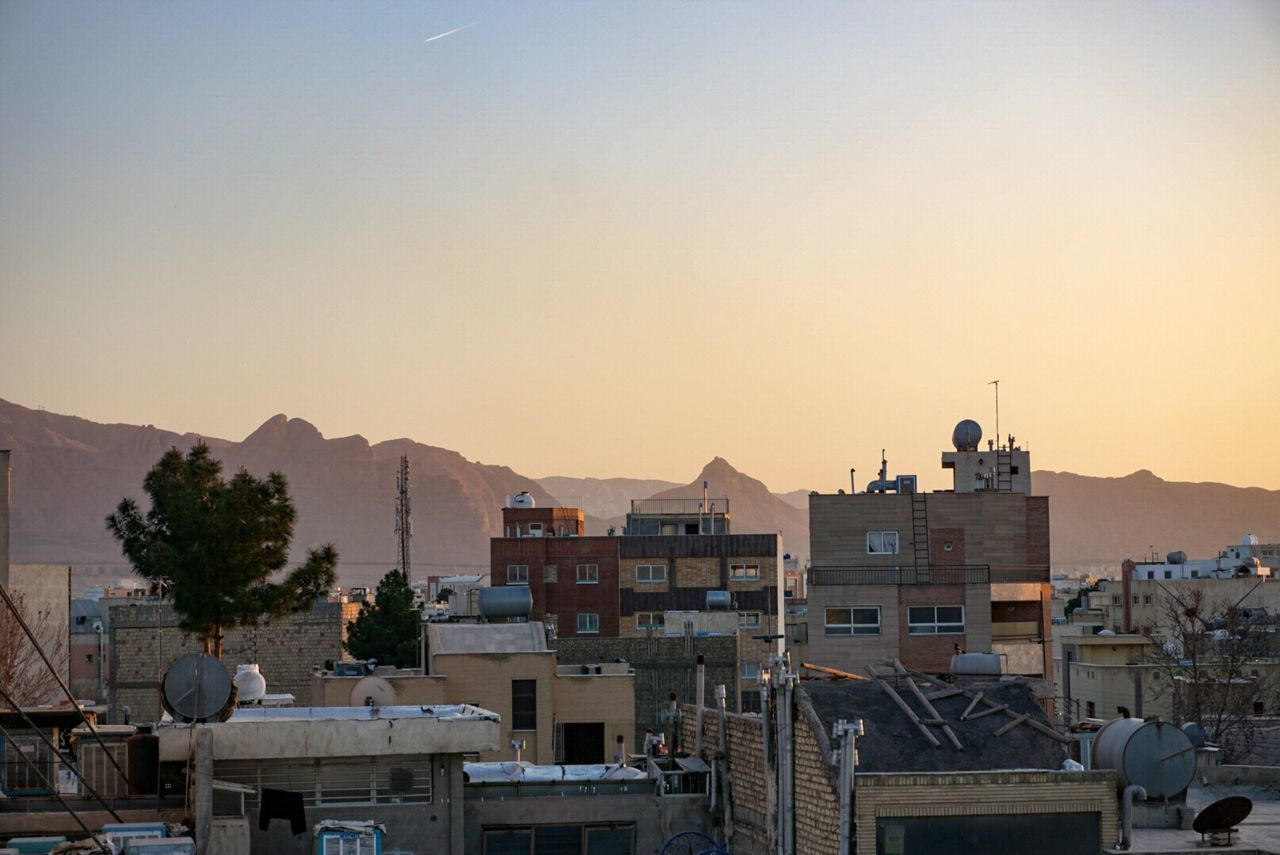 architecture, building exterior, built structure, mountain, sunset, outdoors, no people, sky, clear sky, city, cityscape, nature, day