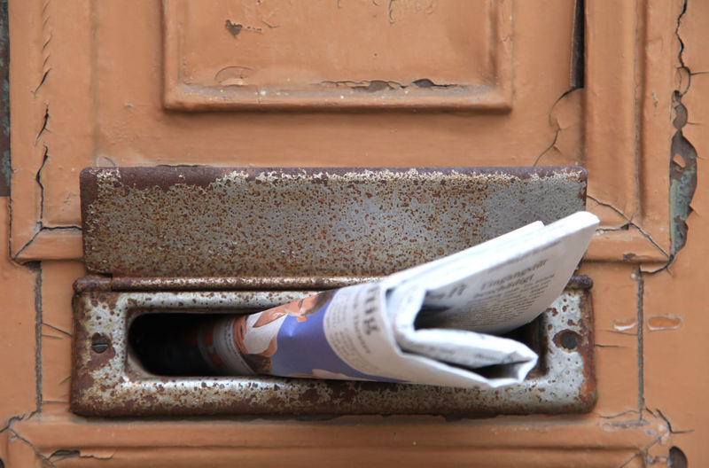 Newspaer in letter slot of door Letter Box Weathered Wood Close-up Day Door Folded Letter Slot Mailbox Mailslot Metal Newspaper No People Outdoors Paper Rusty