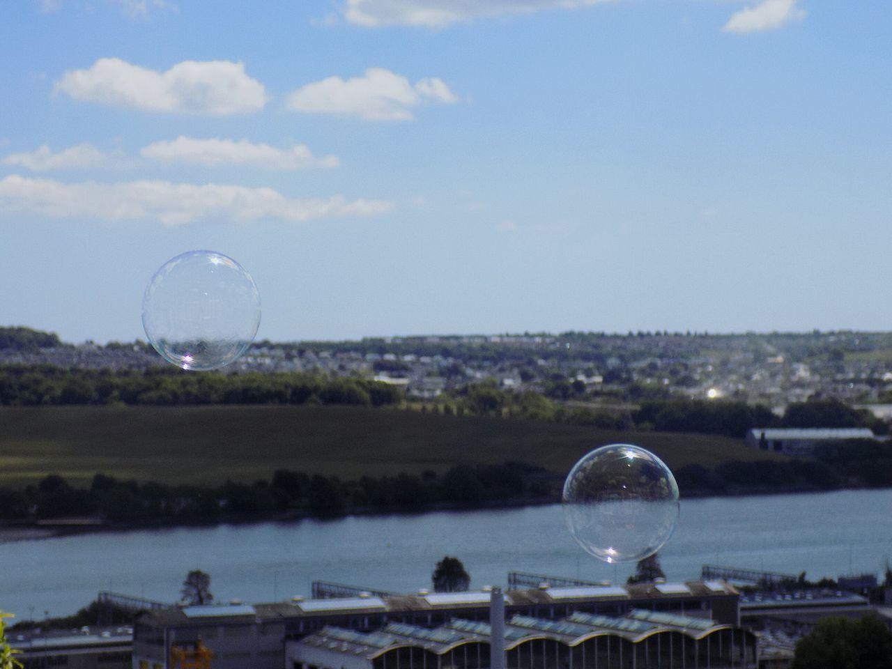 Close-Up Of Bubbles Over Lake And Town Against Blue Sky