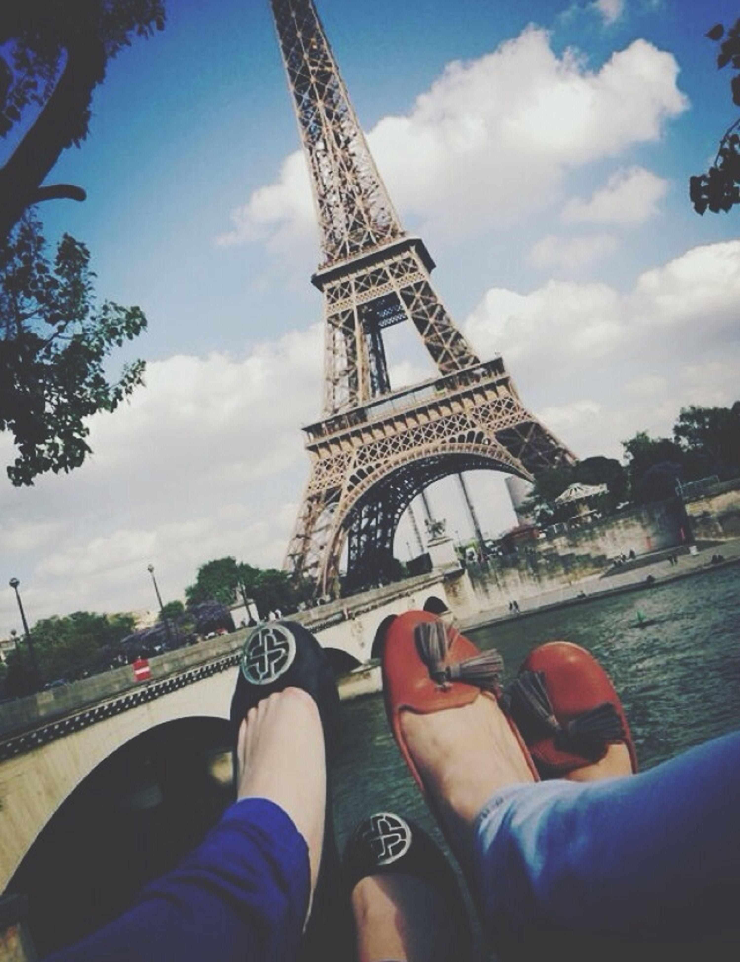 architecture, built structure, lifestyles, sky, tower, international landmark, famous place, leisure activity, eiffel tower, tourism, travel destinations, men, travel, capital cities, personal perspective, tall - high, city, building exterior