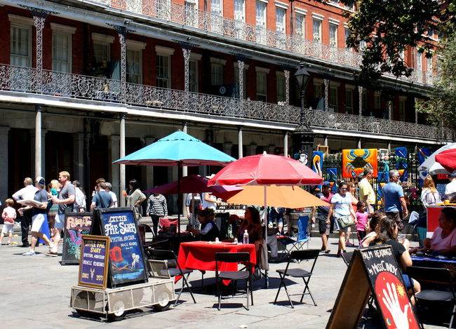 A vibrant and colorful city street scene with art, tourists and fortune teller stalls in New Orleans. Architecture Built Structure City City Life Colorful Day Fortune Telling Jackson Square Lifestyles Market Market Stall Multi Colored Outdoors Palm Reader Railings Sale Street Scene Umbrellas Urban Wrought Iron